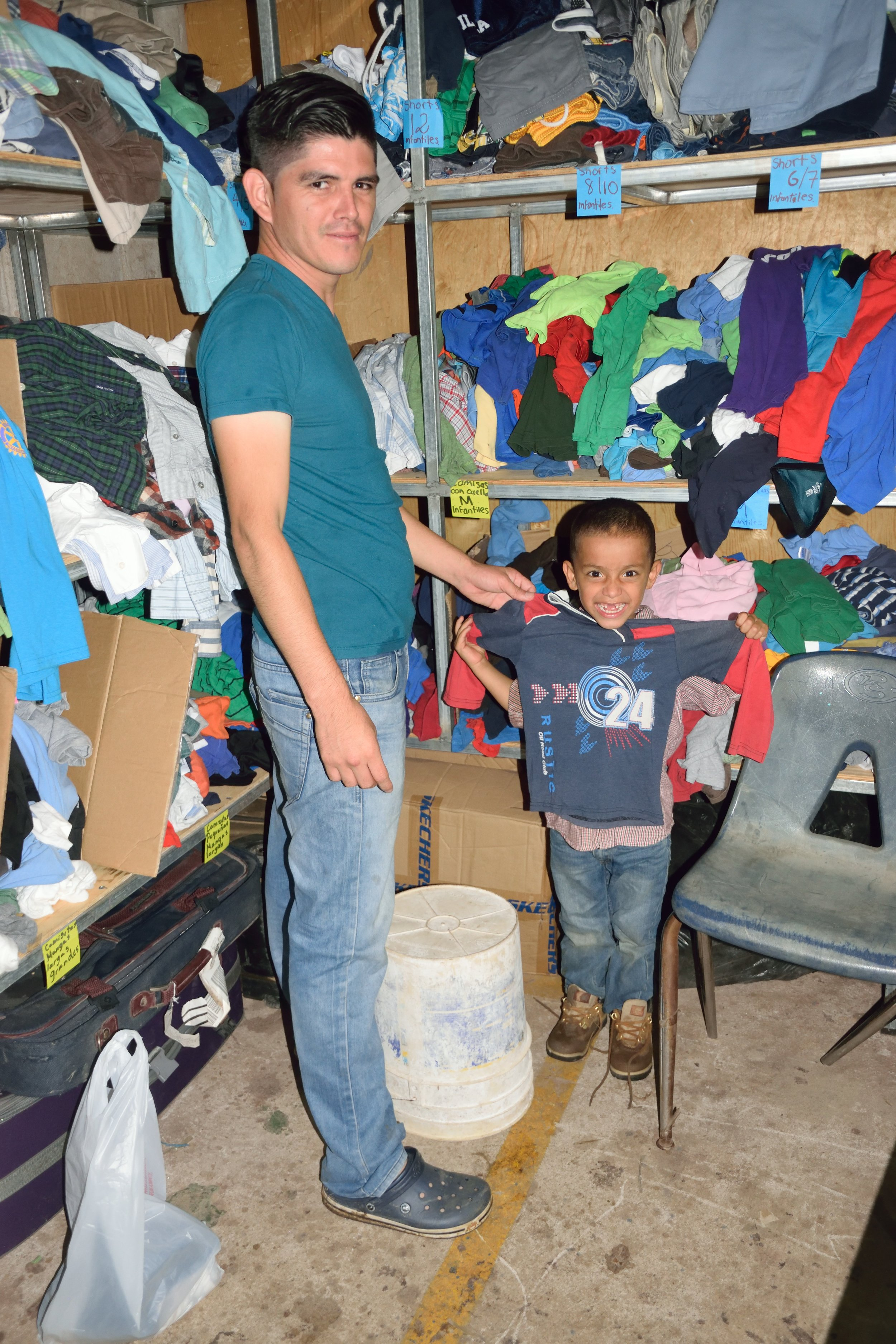 Here, one of our 'padrinos' helps one of the young boys in 'hogar' 5 try on and pick out a new shirt!