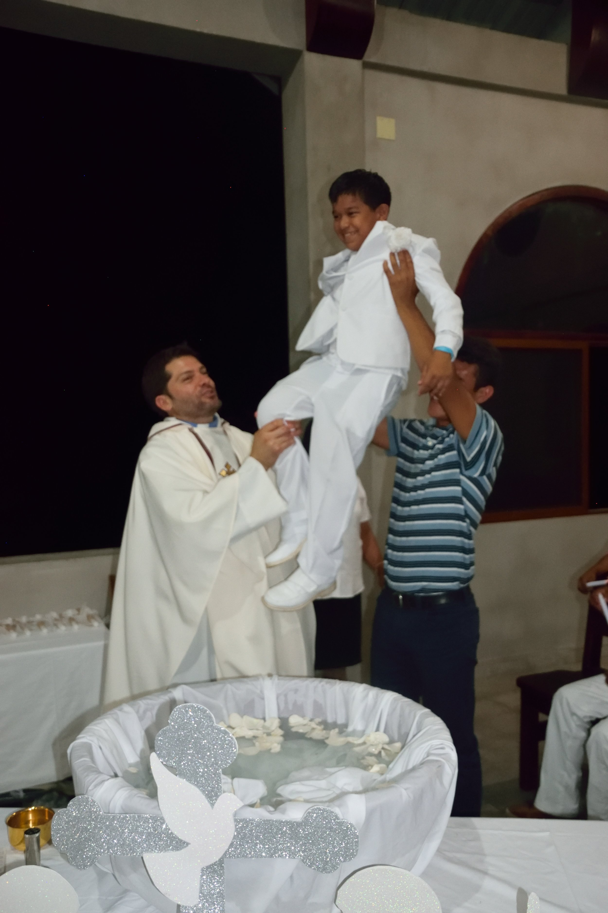 Alanzo, lifted up by Padre Patricio and one of the older boys he chose to be his godfather, following his baptism this year during 'Semana Santa' (Holy Week).