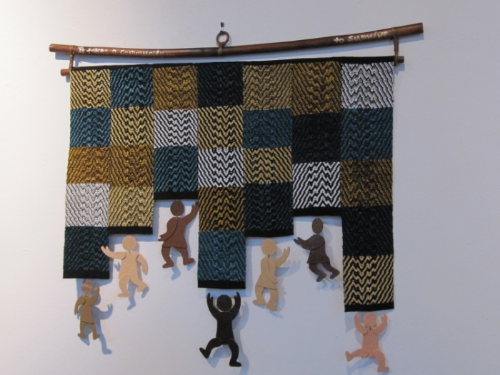 "As partners, Susan Cagan and Fran Nowak, of Valley Vogue Collections combined their talents in wall art. Shown above is their shrinkart and handwoven wall hanging, ""It Takes a Village""."