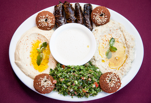 Vegetarian plate at Aleppo's Kitchen Mediterranean restaurant with sprinkled Aleppo pepper on to of the hummus and mutabaal.