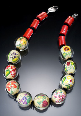 Spring Flowers   Hand-painted encased glass beads, coral, sterling leaf clasp. Length: 17″