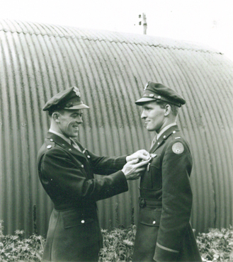 Lieutenant John Simon, pilot of my dad's plane in the 492nd, awarding him a medal—not sure which one.