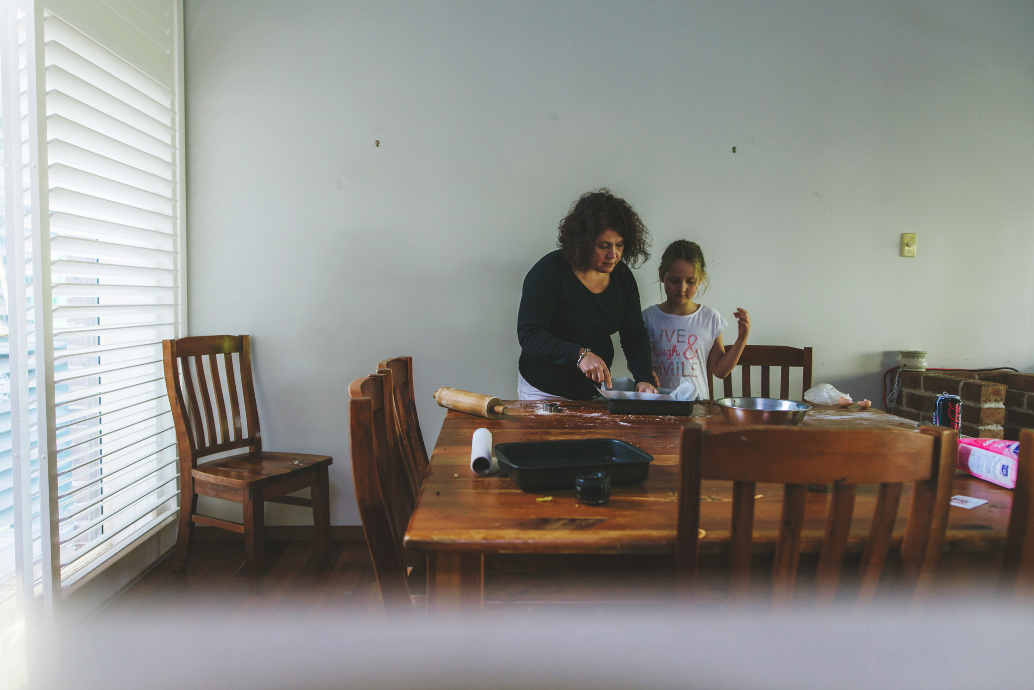Family photography in Sydney by Cindy Cavanagh. A mother and daughter baking in the kitchen.