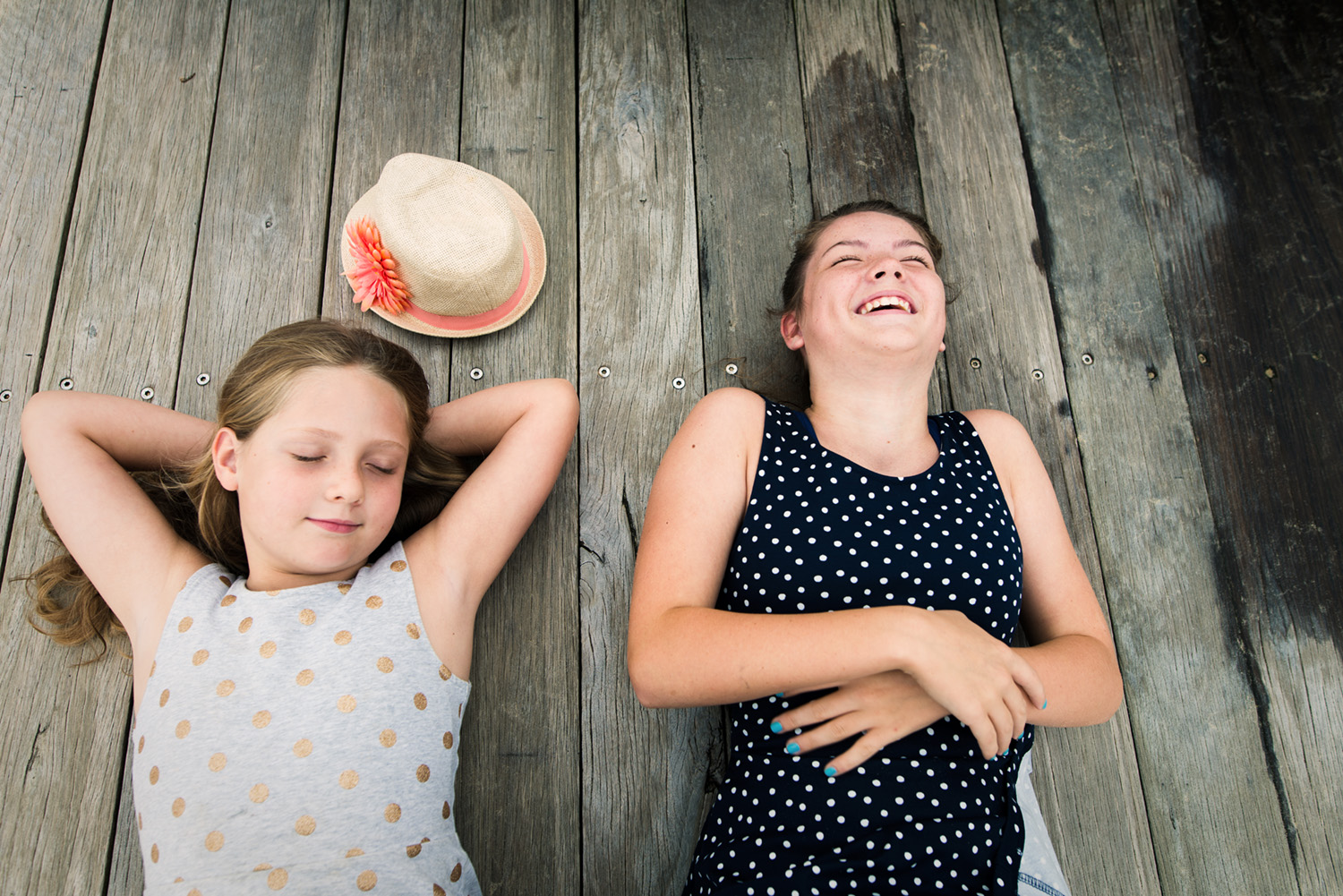 Two sisters laying on a boardwalk