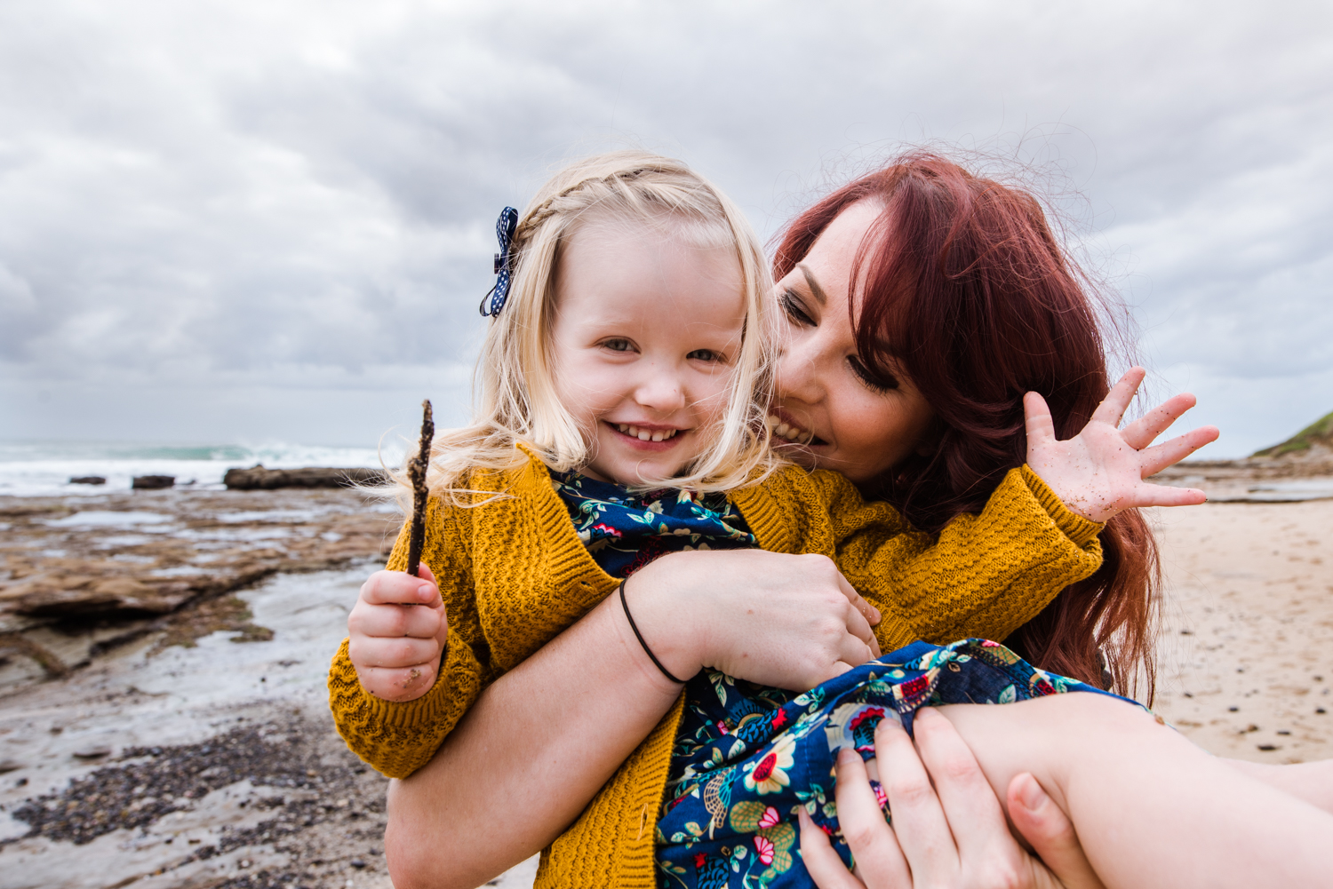 Portrait-of-a-girl-laughing-as-her-Mum-lifts-her-up