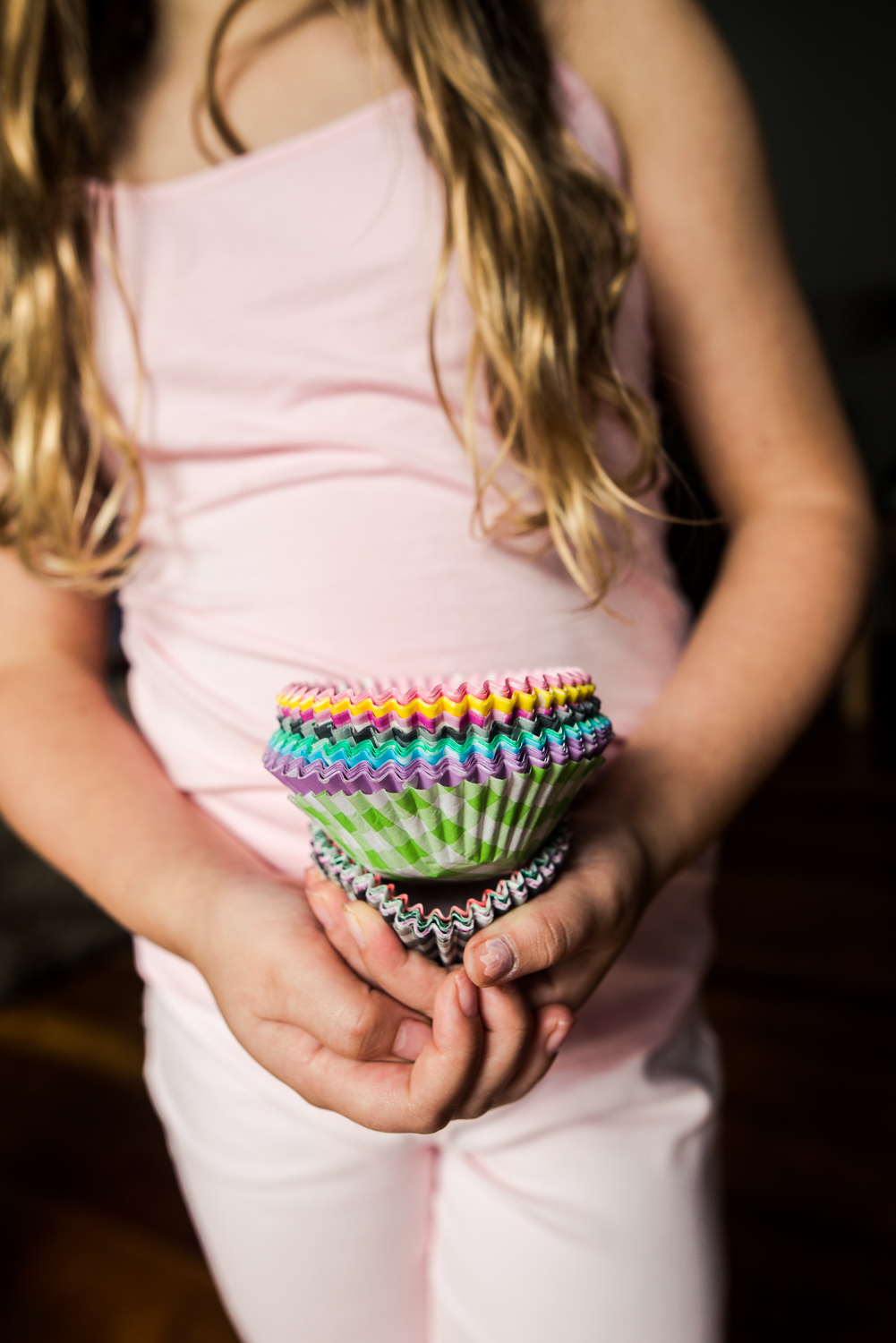 girl hold colourful cupcake cases