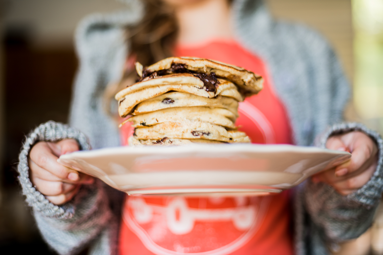 A girl proudly displays a stack of pancakes which she made for her family.