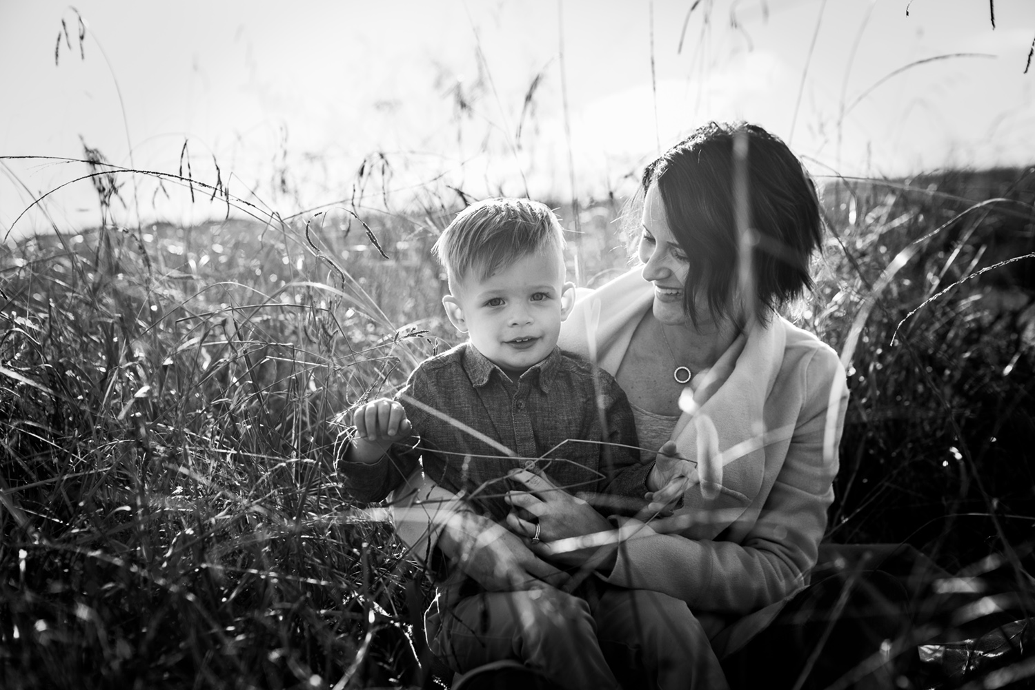 A beautiful moment captured during a motherhood portrait session in Sydney as a toddler and his Mum cuddle in the long grass at Rouse Hill Regional Park.