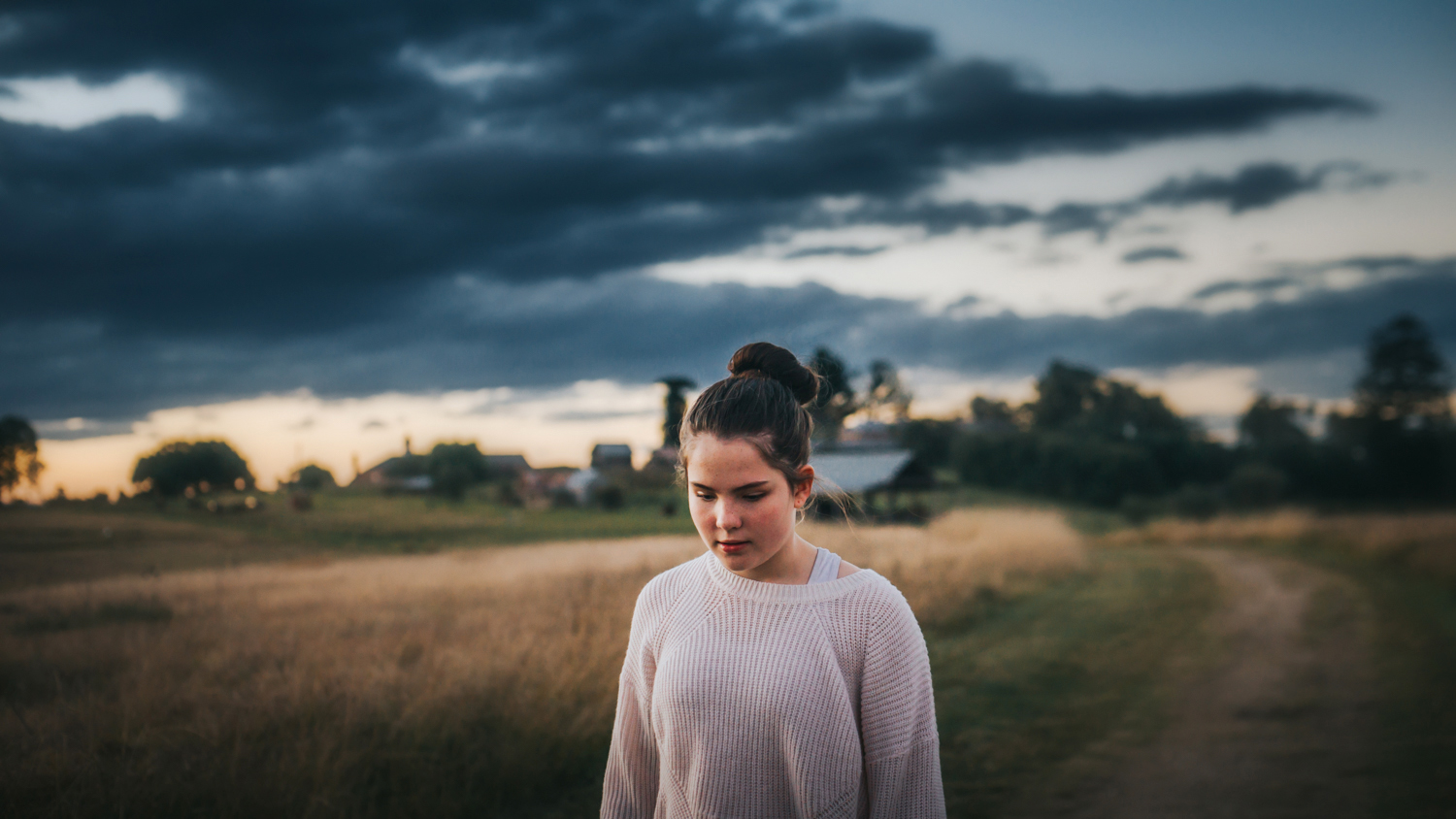 An emotive lifestyle portrait of a teenage girl walking through a field of grass at sunset in Rouse Hill, Sydney.