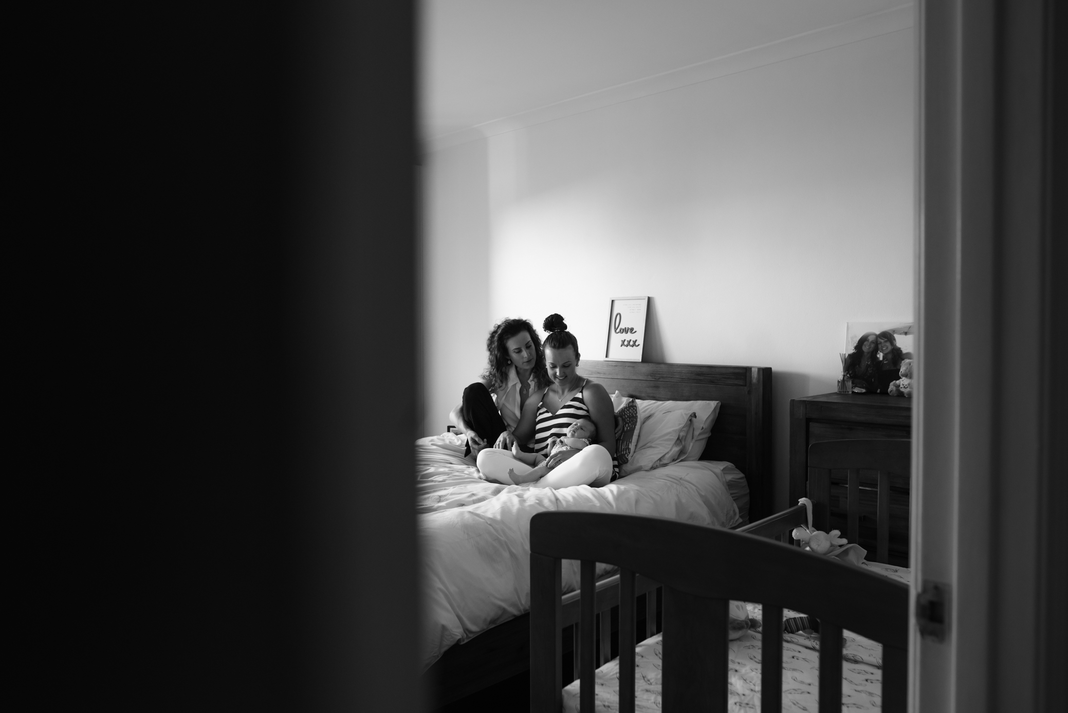 sydney-family-photographer-a-family-embraces-and snuggles-with-their-newborn-baby
