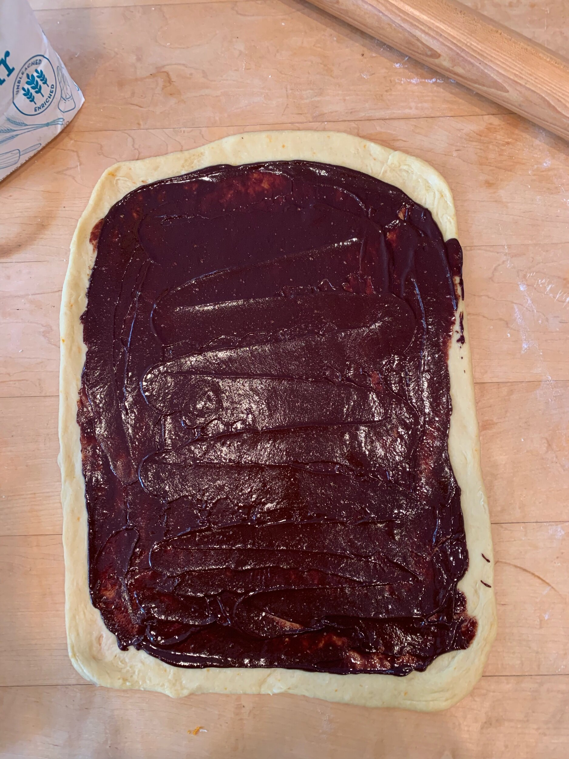 Roll the dough and then spread with the chocolate filling.