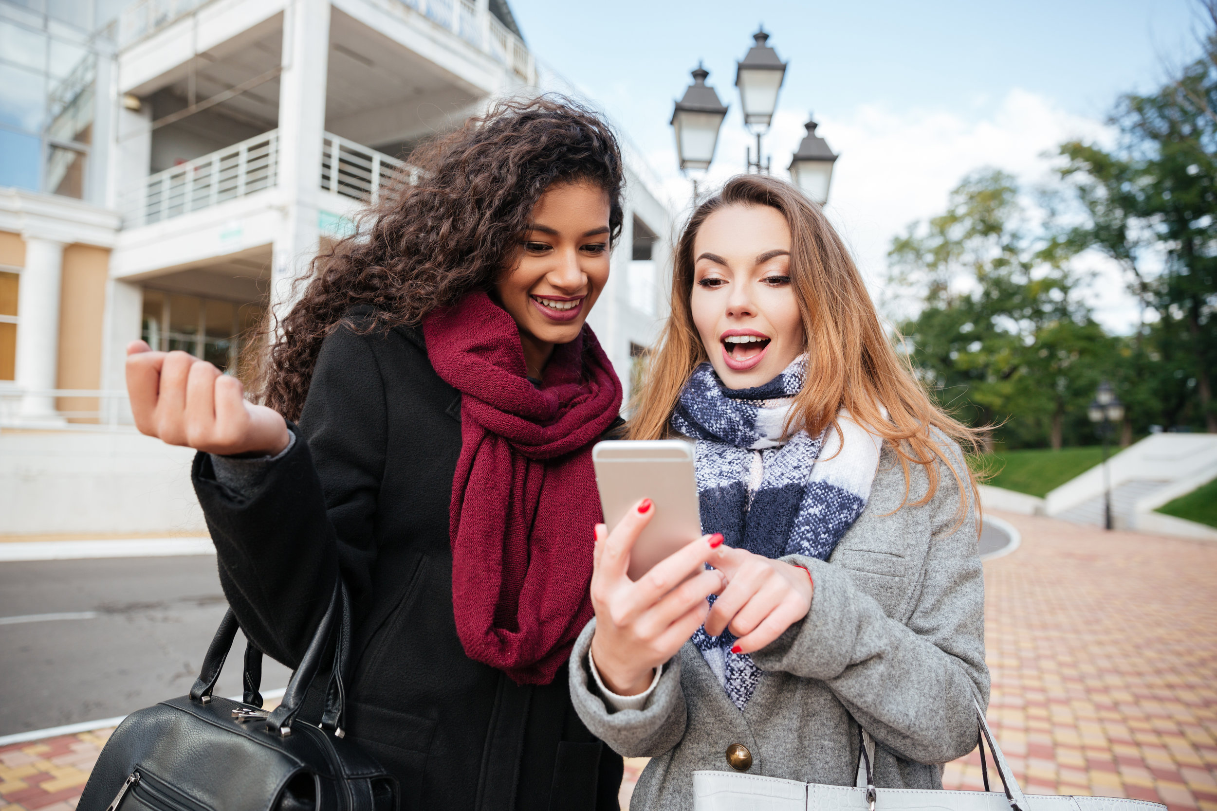 graphicstock-euphoric-friends-watching-videos-on-a-smartphone-and-pointing-at-screen-surprised-caucasian-girl-wearing-scarf-in-a-cage-print-african-lady-wearing-burgundy-scarf_rOfaSaKUhg.jpg