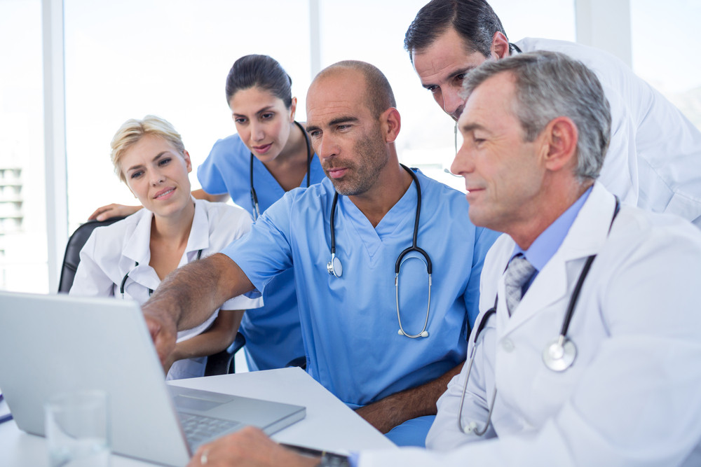 stock-photo-doctor-showing-laptop-pc-to-his-colleagues-in-medical-office-288533741.jpg