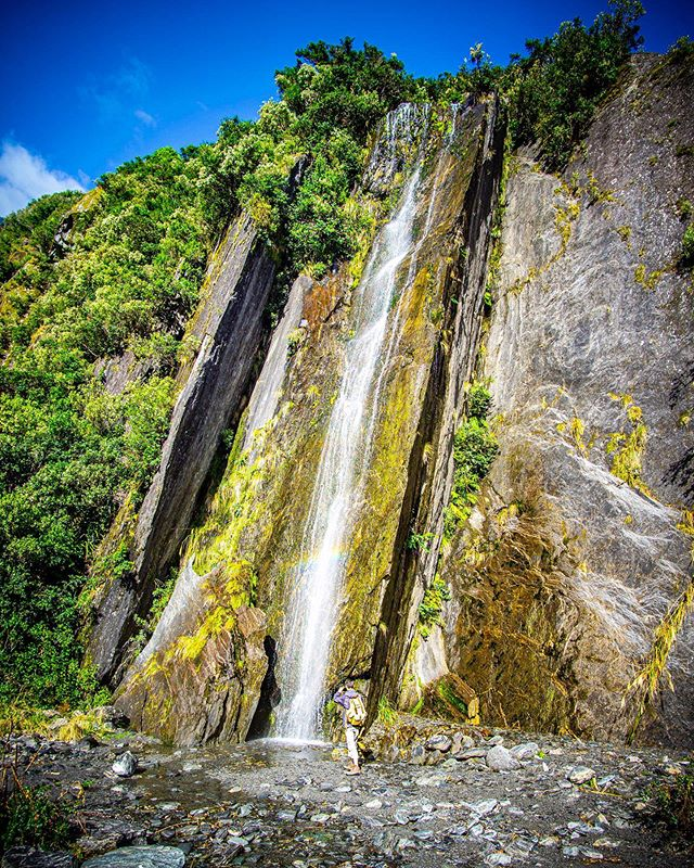 A sneaky 🌈 rainbow through this waterfall near the Franz Joseph Glacier Feb 2019, and @chidge_over_troubled_water getting right in there for a close up. • • • #waterfall #water #rainbow #cliff #glacier #newzealand #nzsouthisland #travel #outdoors #roadtrip #nature #naturelovers #sonya6000 #samyang12mmf2 @purenewzealand @new_zealand_landscapes @newzealandguide