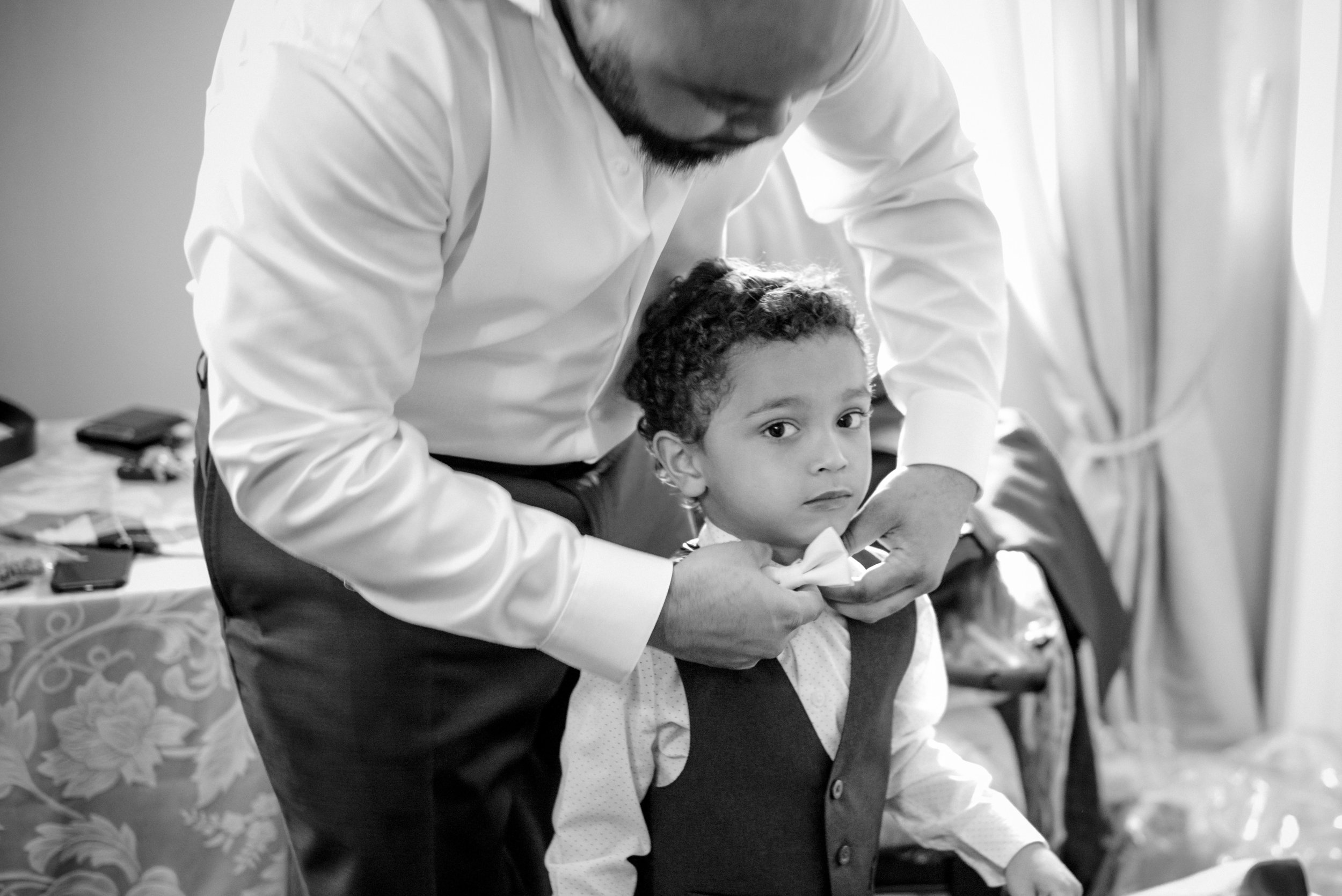 Groom helping ring bearer with his bow tie