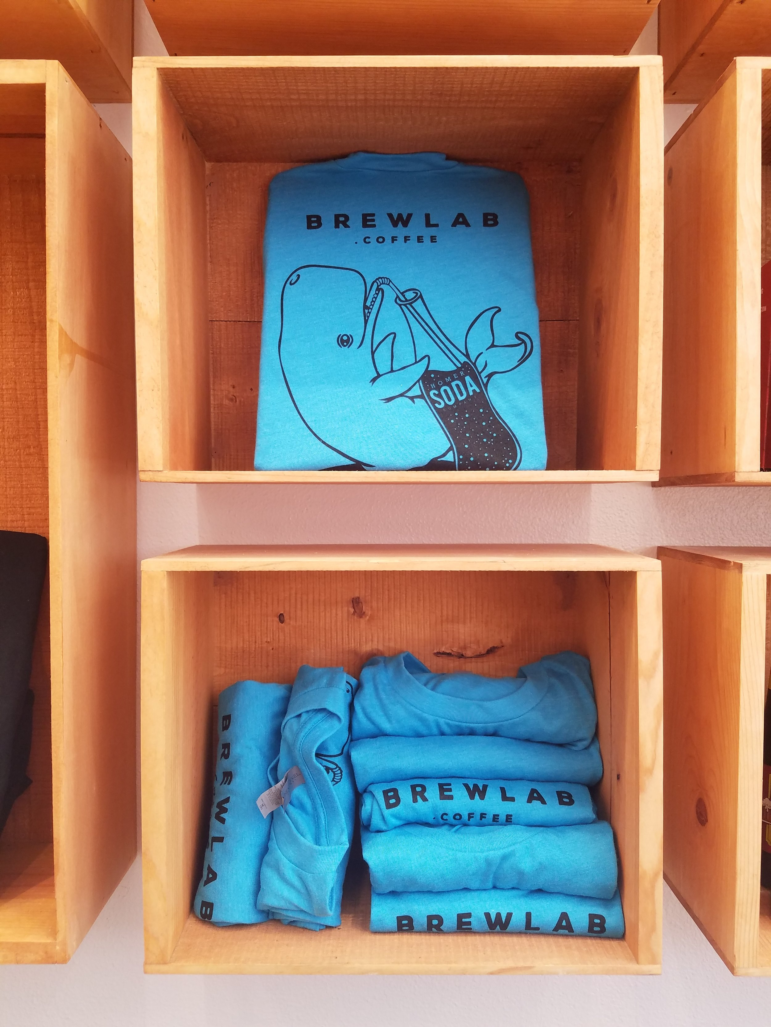 A kid's t-shirt design. A baby whale drinking a Homer Soda Company beverage, which are sold in Brewlab.