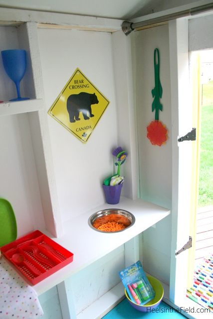 By cutting a hole in the makeshift counter and dropping in a small metal bowl - it's now a perfect little play sink!
