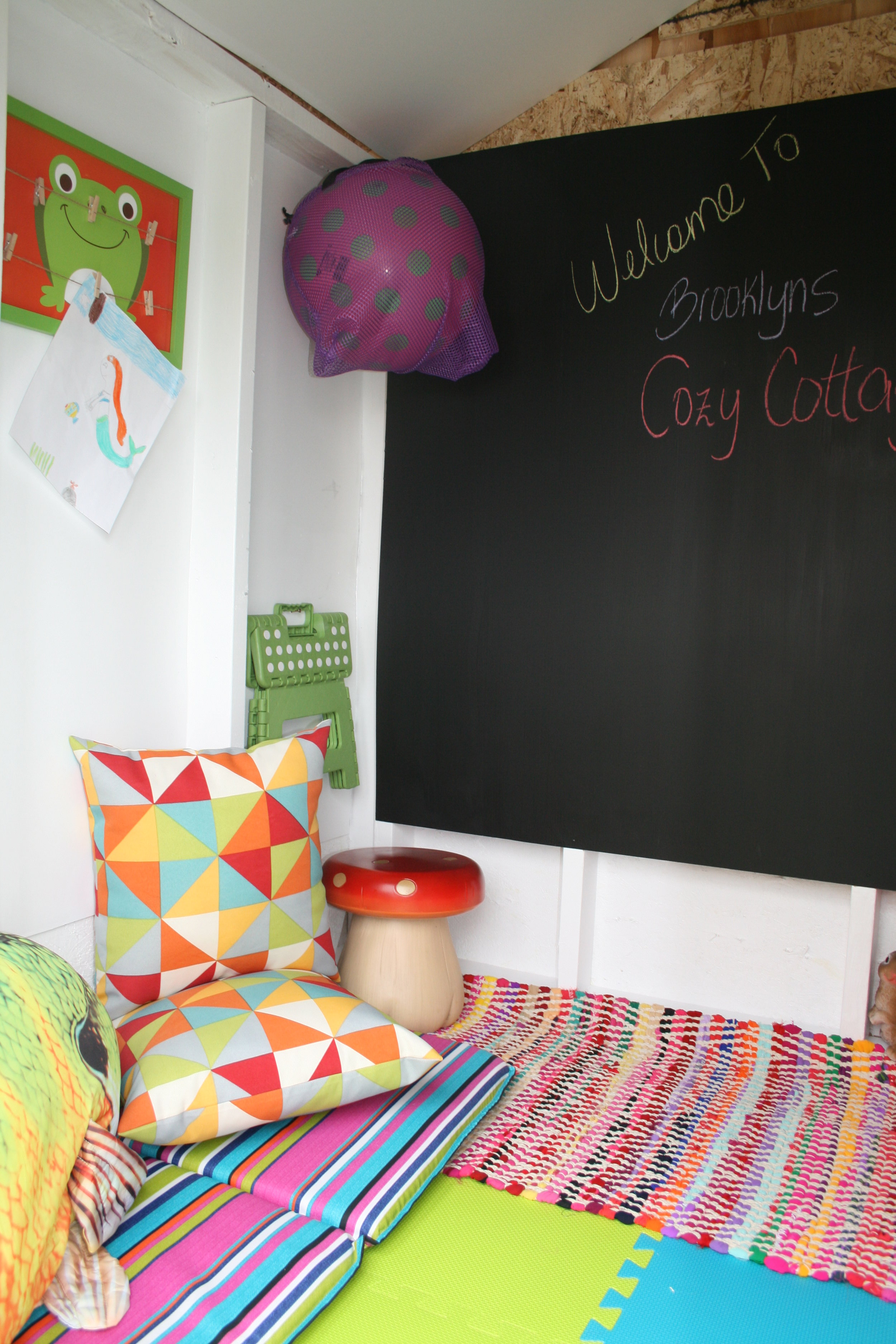 Comfy colourful outdoor pillows, mats & rug along with this  must have  mushroom stool create a cozy lounging area to chat and play. The wall area can be used to display art to.
