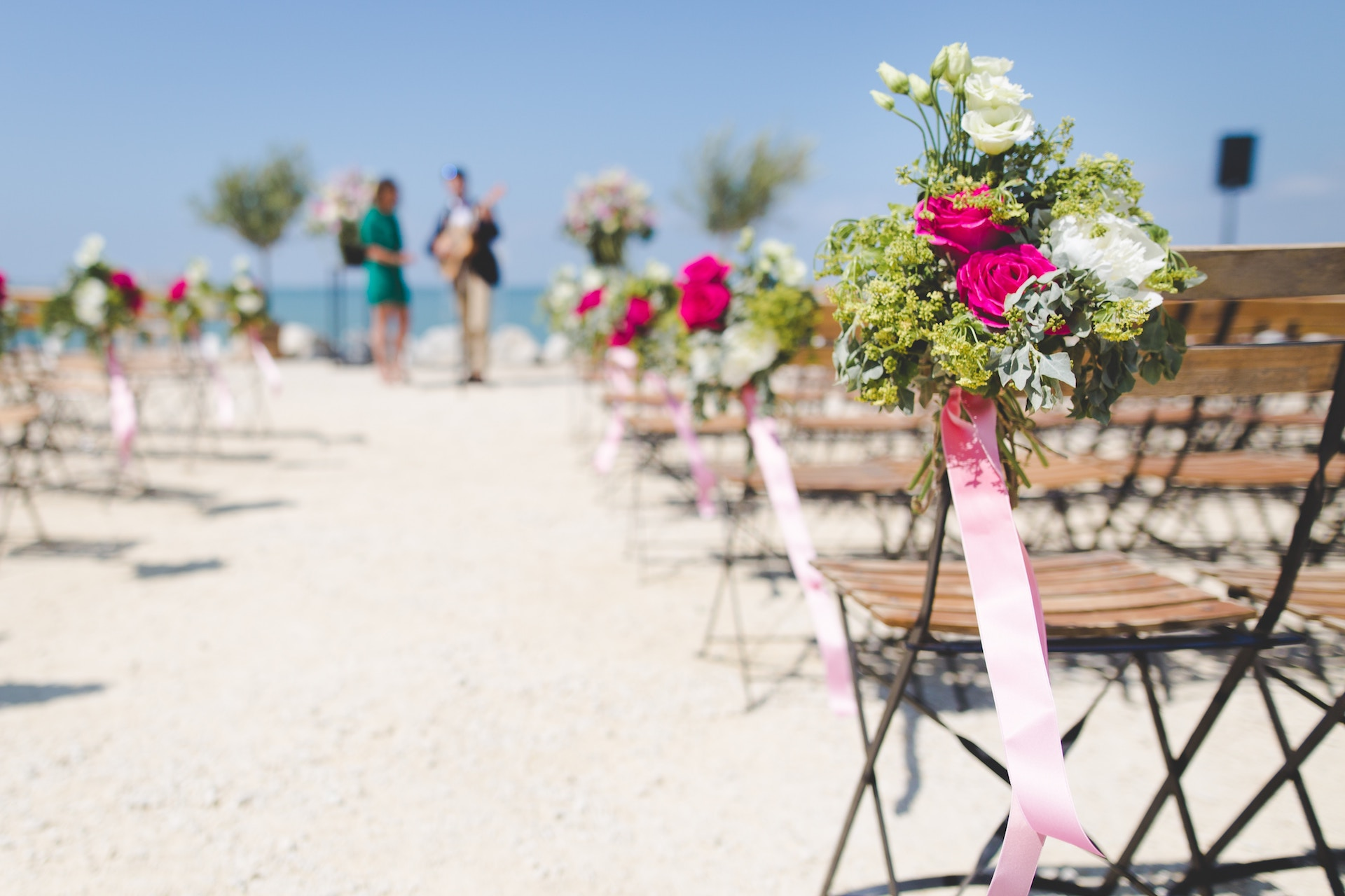 beach wedding chairs with pink and green flowers.jpg