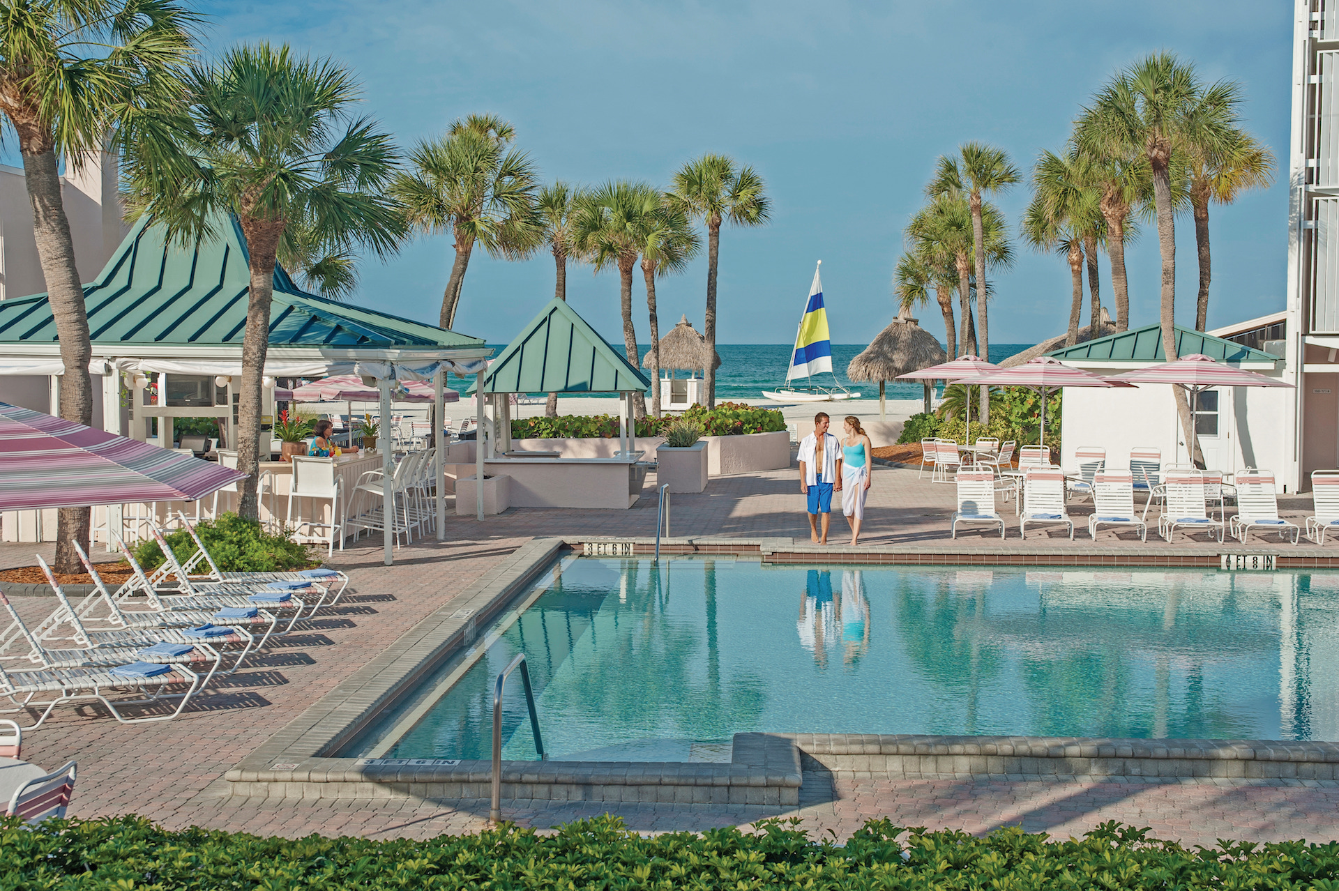 couple holding hands in front of pool at Sandcastle Resort at Lido Beach.jpg