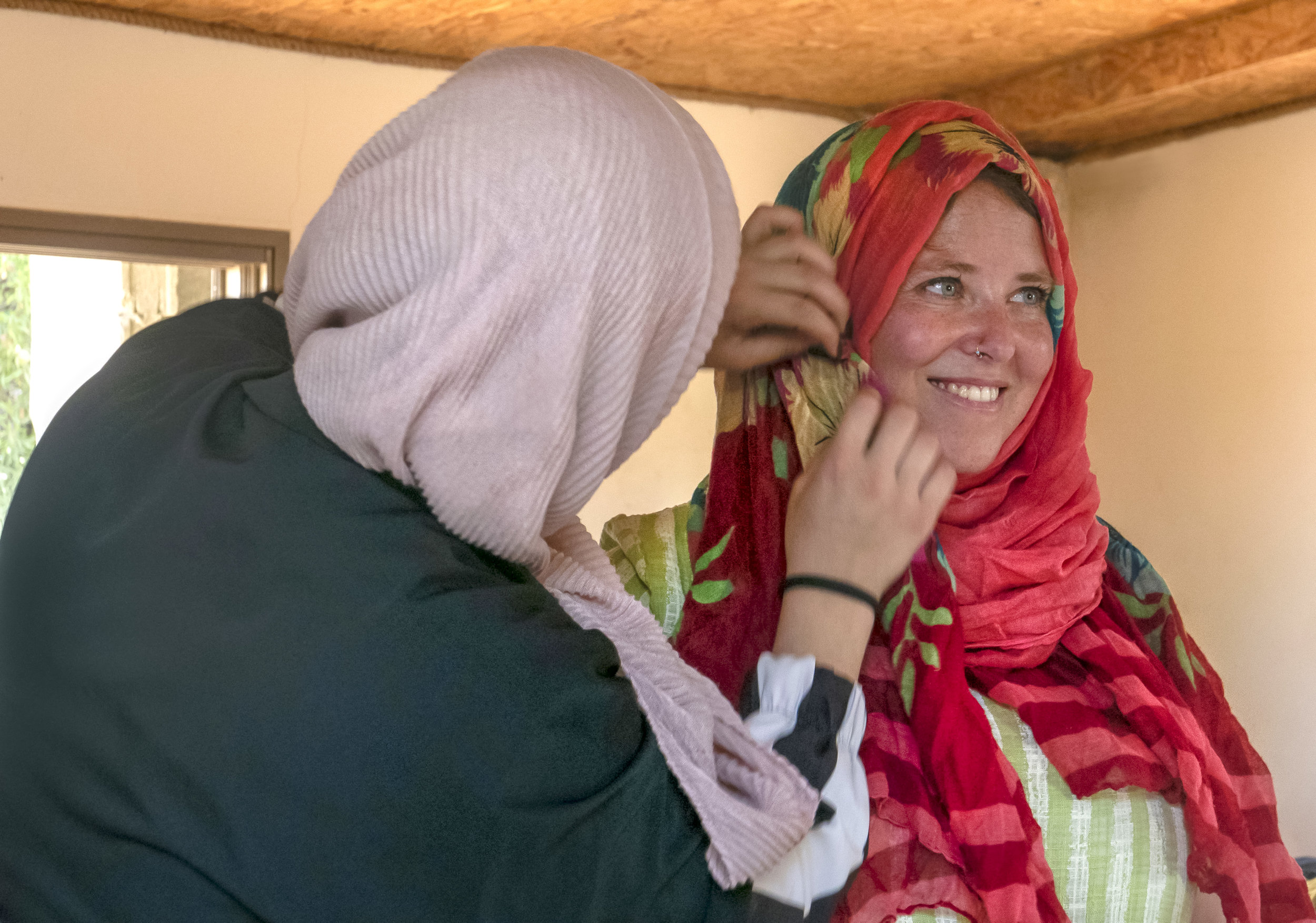 A Palestinian participant wraps an Israeli participant's headscarf in the hijab manner, all with light humour and good faith