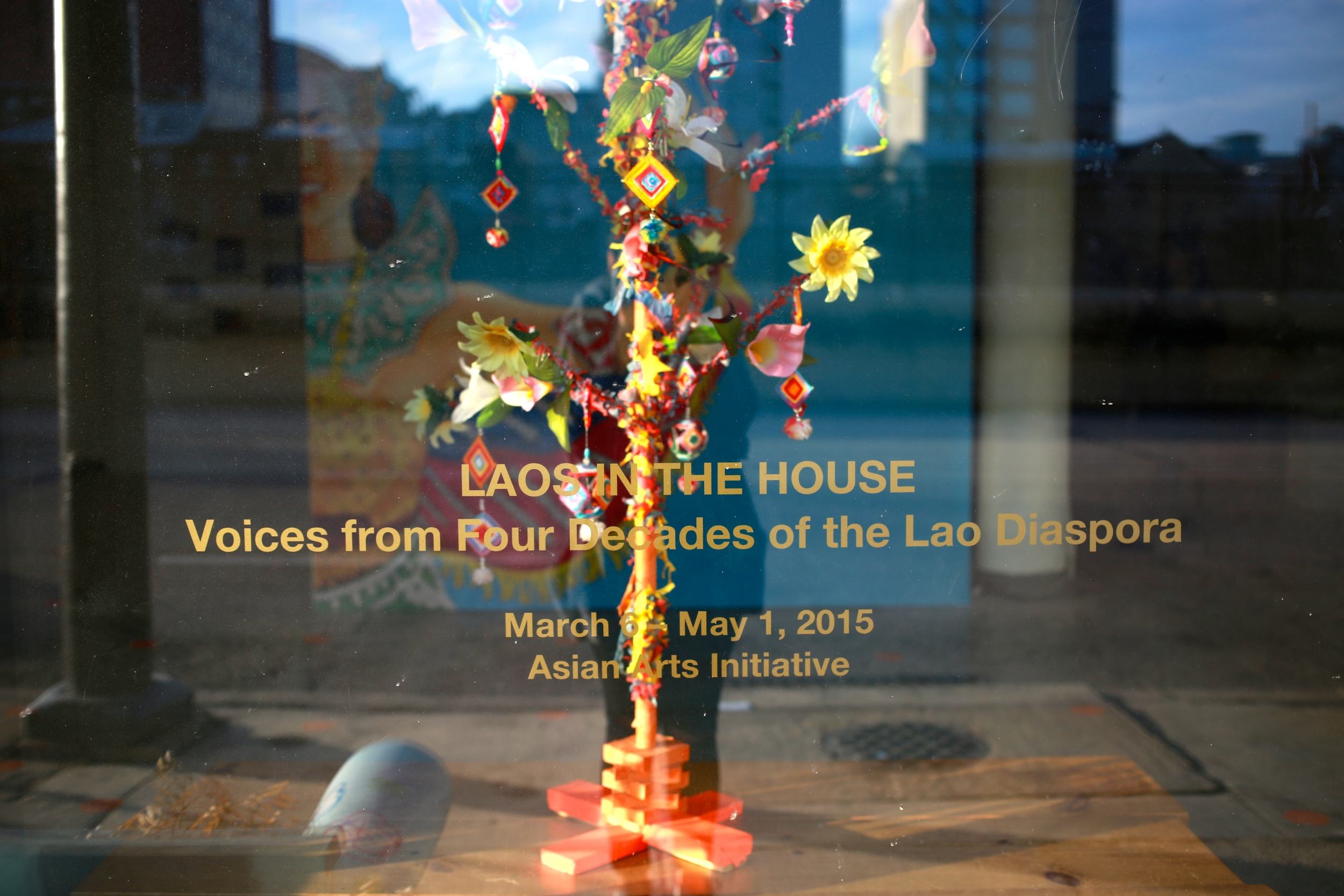 "Front view of the Asian Arts Initiative gallery window with a ""money tree"" on loan courtesy of Wat Lao Phouthathammaram"