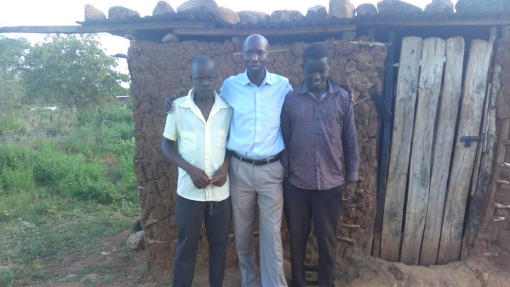 Wilson Kipsang (Kenyan athlete) pictured with Vincent and Kipchumba in front of the house they sleep in.