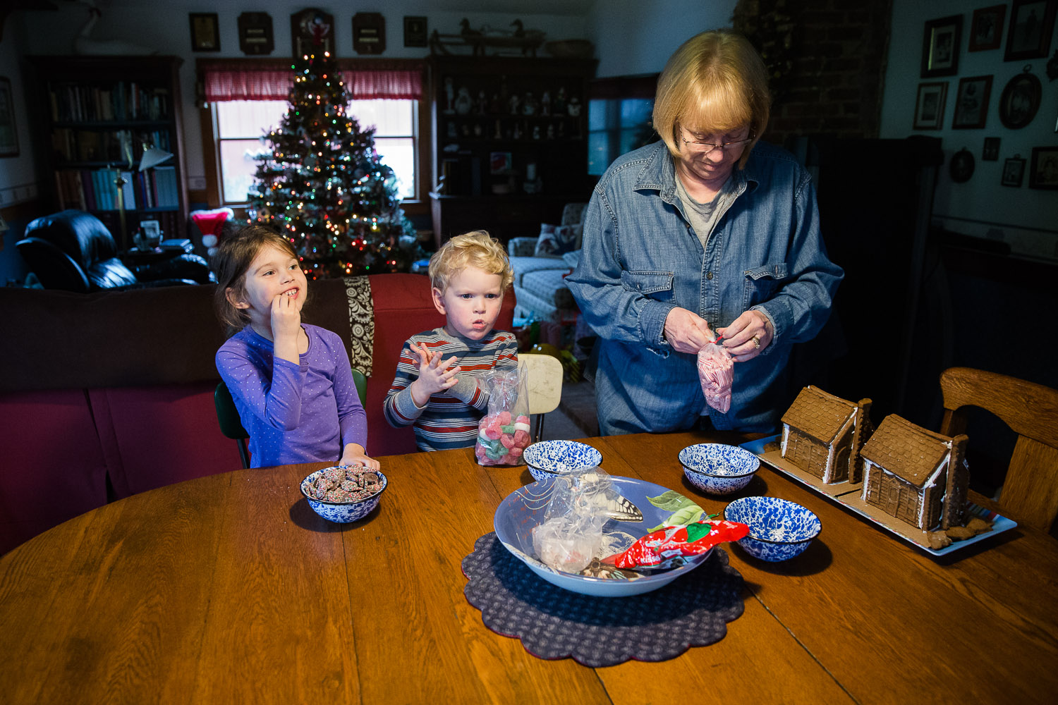 Grandchildren decorate gingerbread houses with their grandparents; family photojournalism