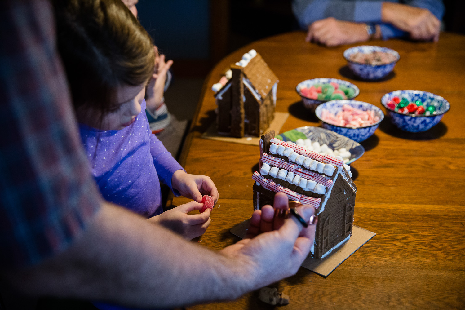 A little girl decorates a gingerbread house with her grandparents; family storytelling photography.