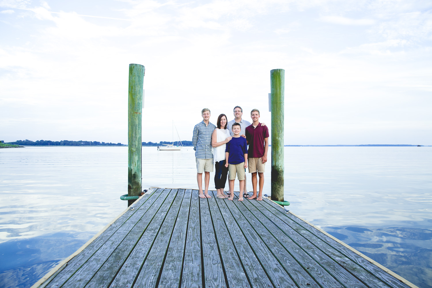 Family stands on pier along the Chester River at the Rock Hall Yacht Club