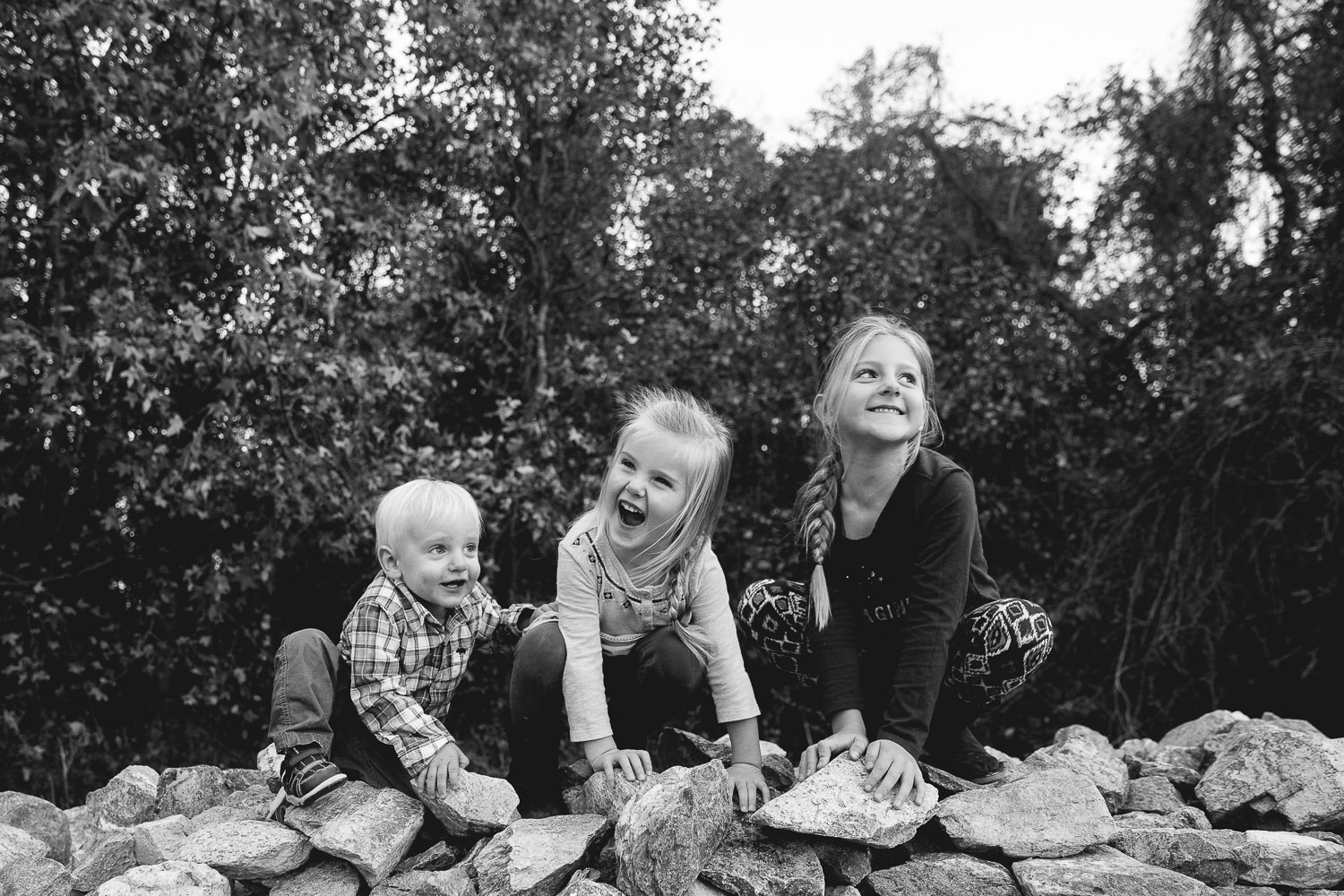 Three children play on a mountain of rocks in Kent County