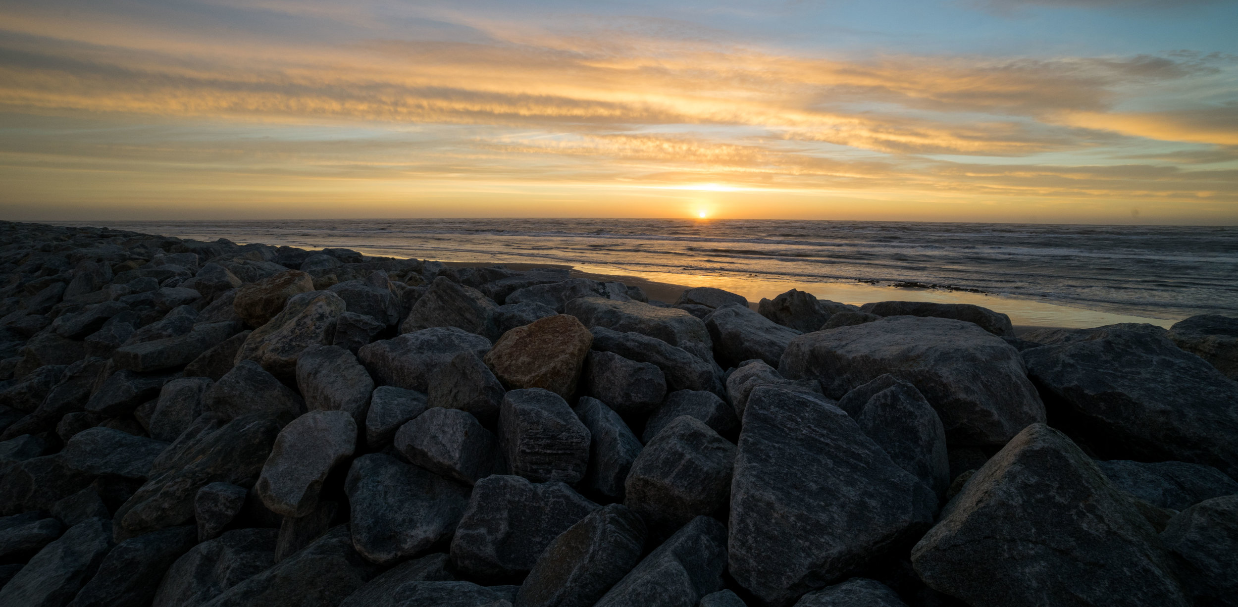 The sea wall, just like the coast, is gradually wearing away.