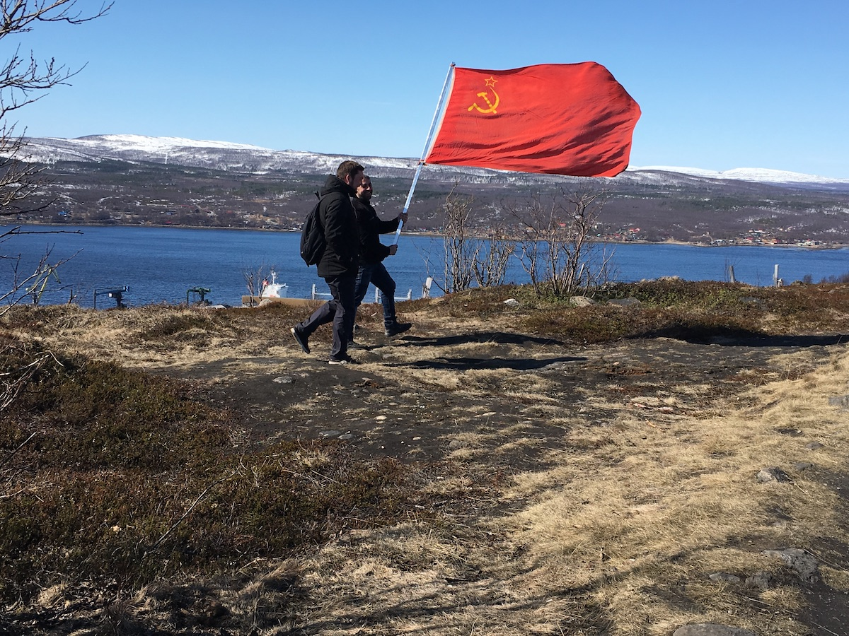 Two men carry a Soviet flag.