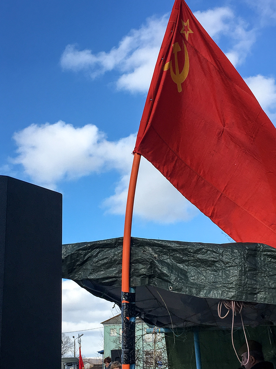 The old Soviet flag waves in the breeze on Victory Day.