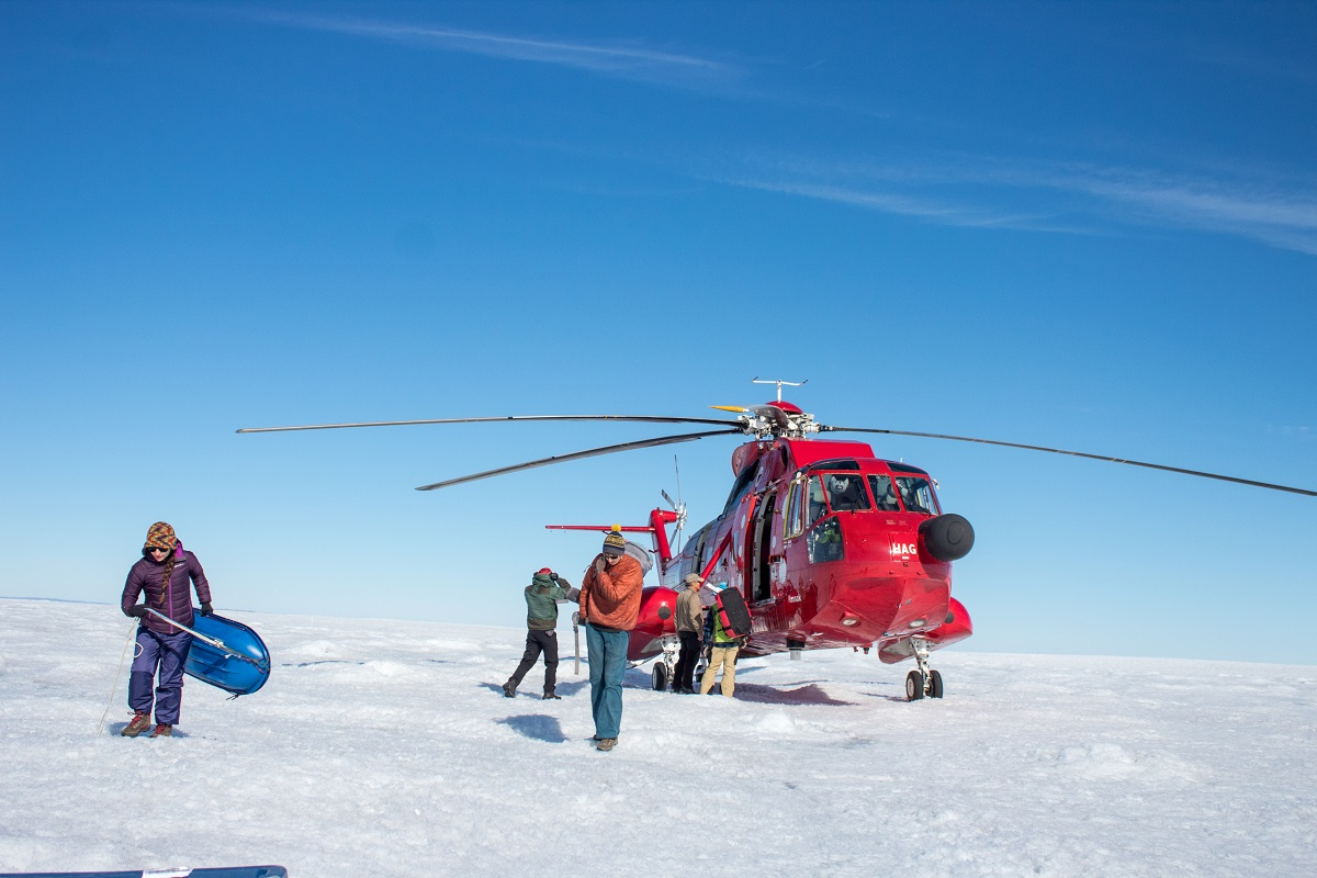 A team of three professors and three students unload the helicopter at their research site on the Greenland ice sheet.