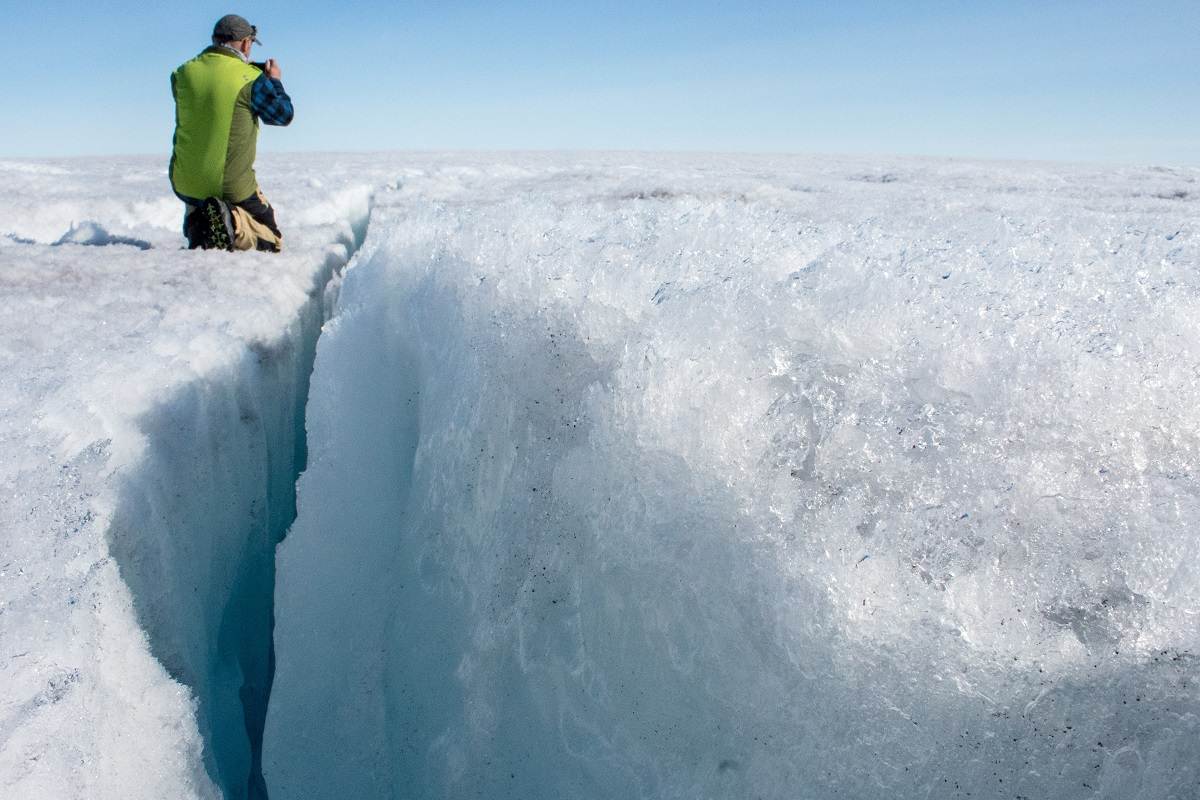 University of Montana glaciologist Joel Harper examines a deep crack in the ice sheet called a crevasse.
