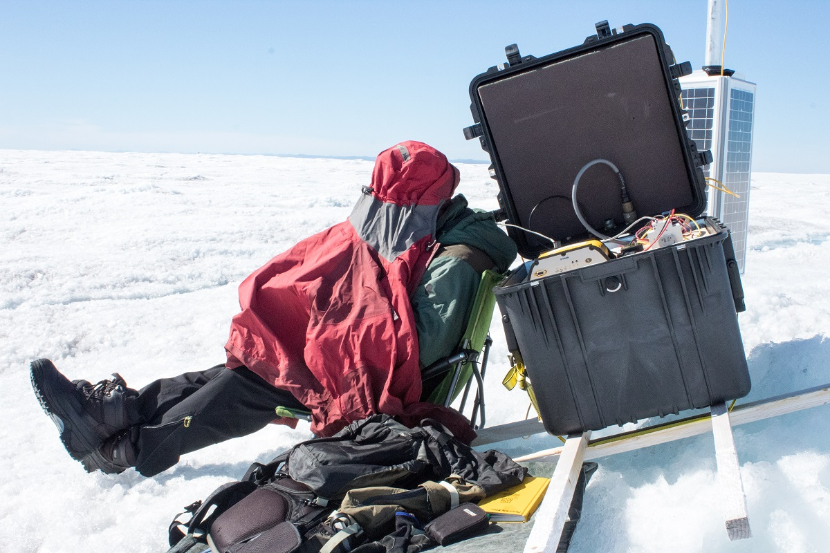 The 24-hour sunlight is so bright that researcher Toby Meierbachtol had to make a tent over his head in order to see the screen of a computer they're using to log the data from the ice sheet bed.