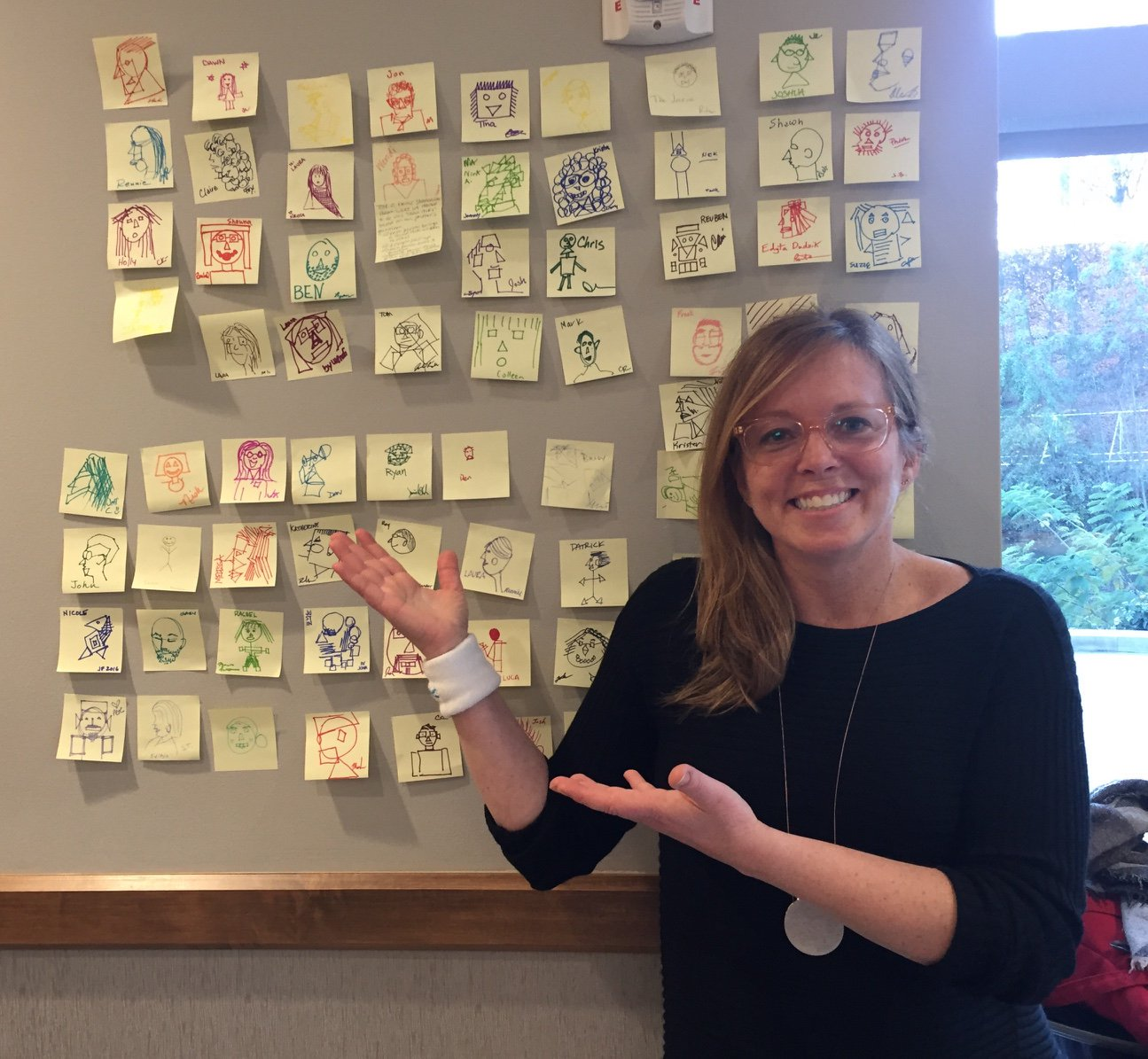 Shannon with drawings made by participants in a workshop she led at World UX (User Experience)Day.