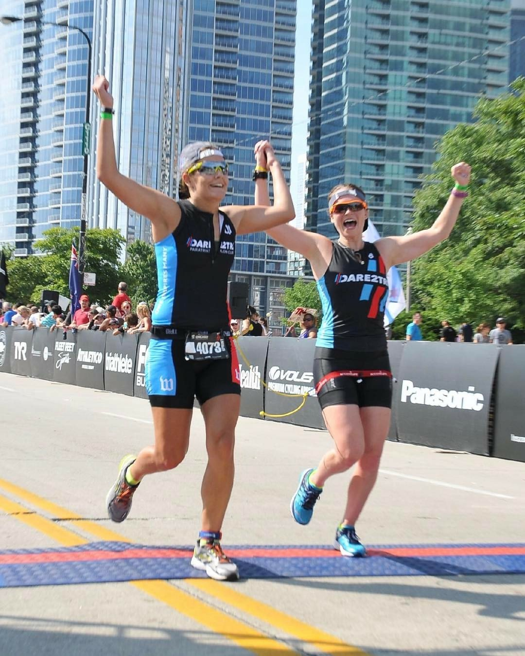 Caroline, at right, crossing the finish line of a triathlon as a guide for visually impaired athletes.