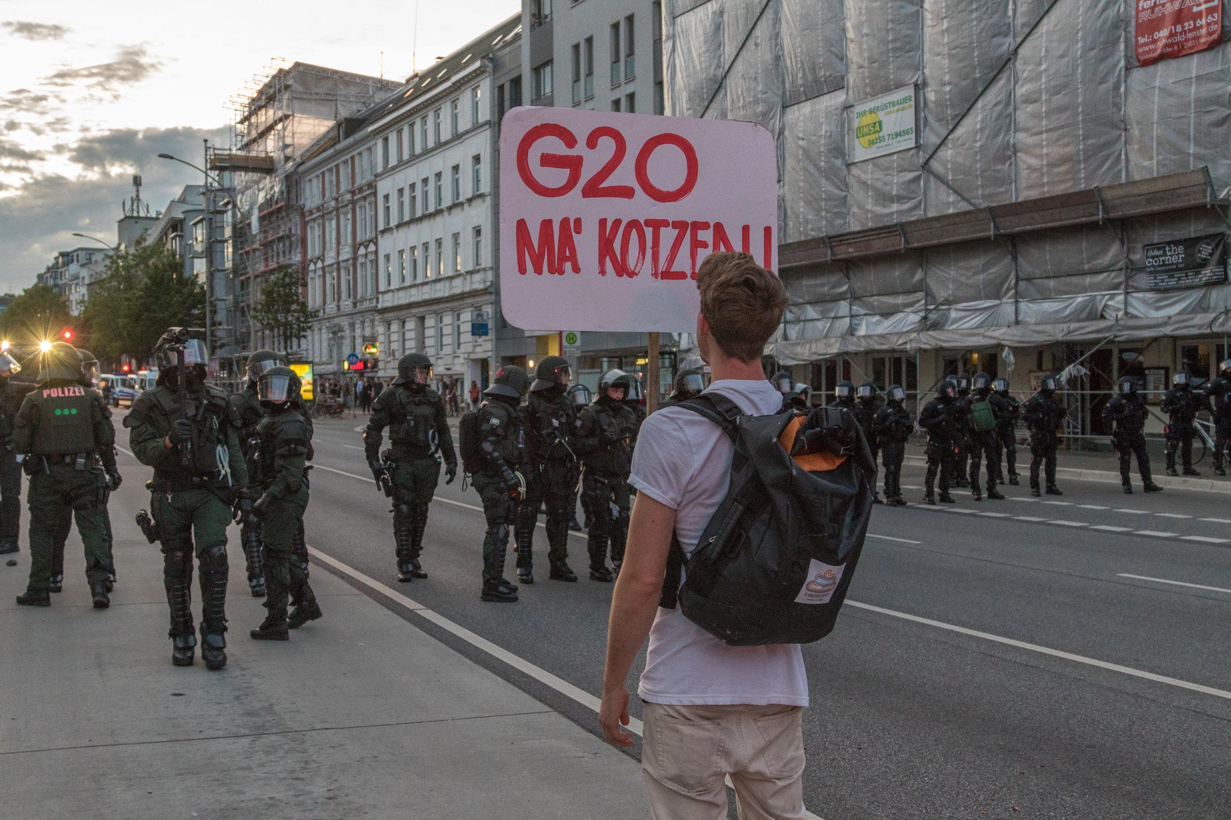 Demonstrant mit Schild vor Polizeikette.jpg