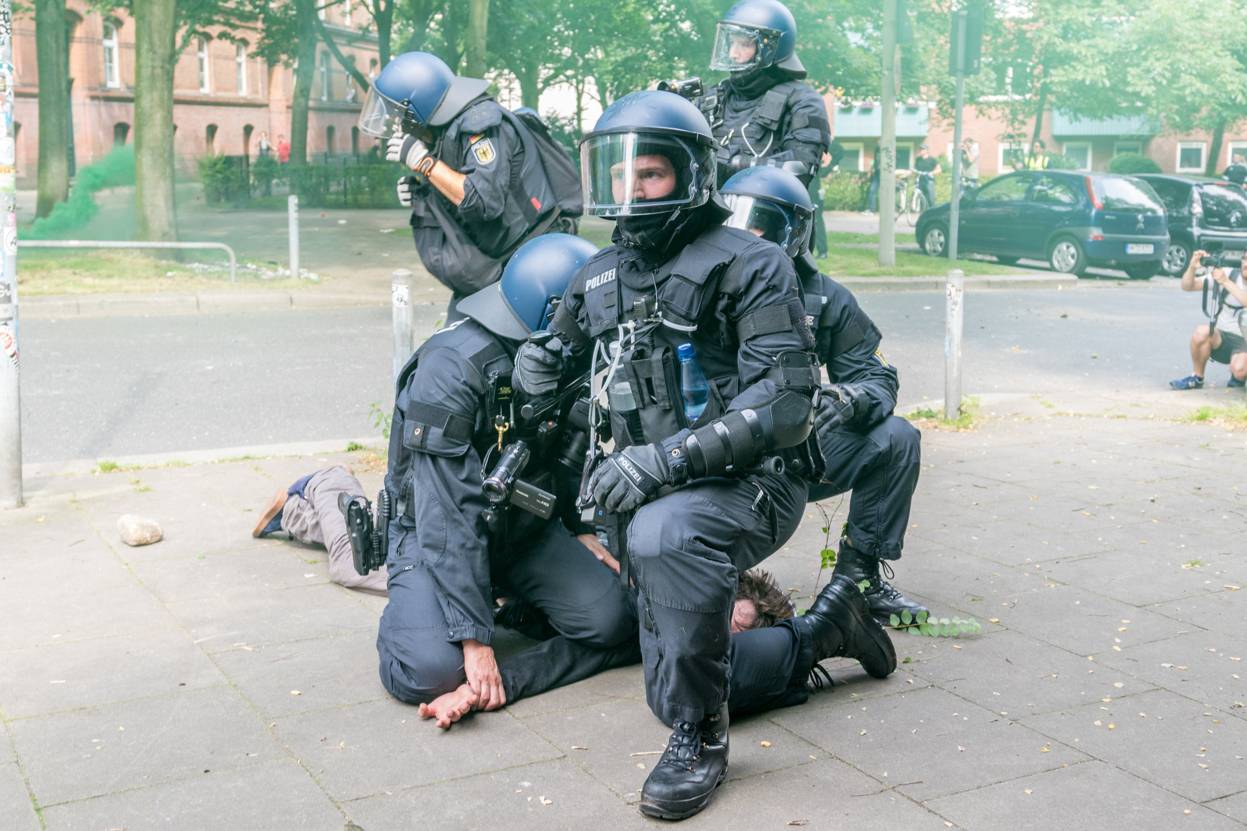 behelmte Polizisten nehmen Mann fest.jpg