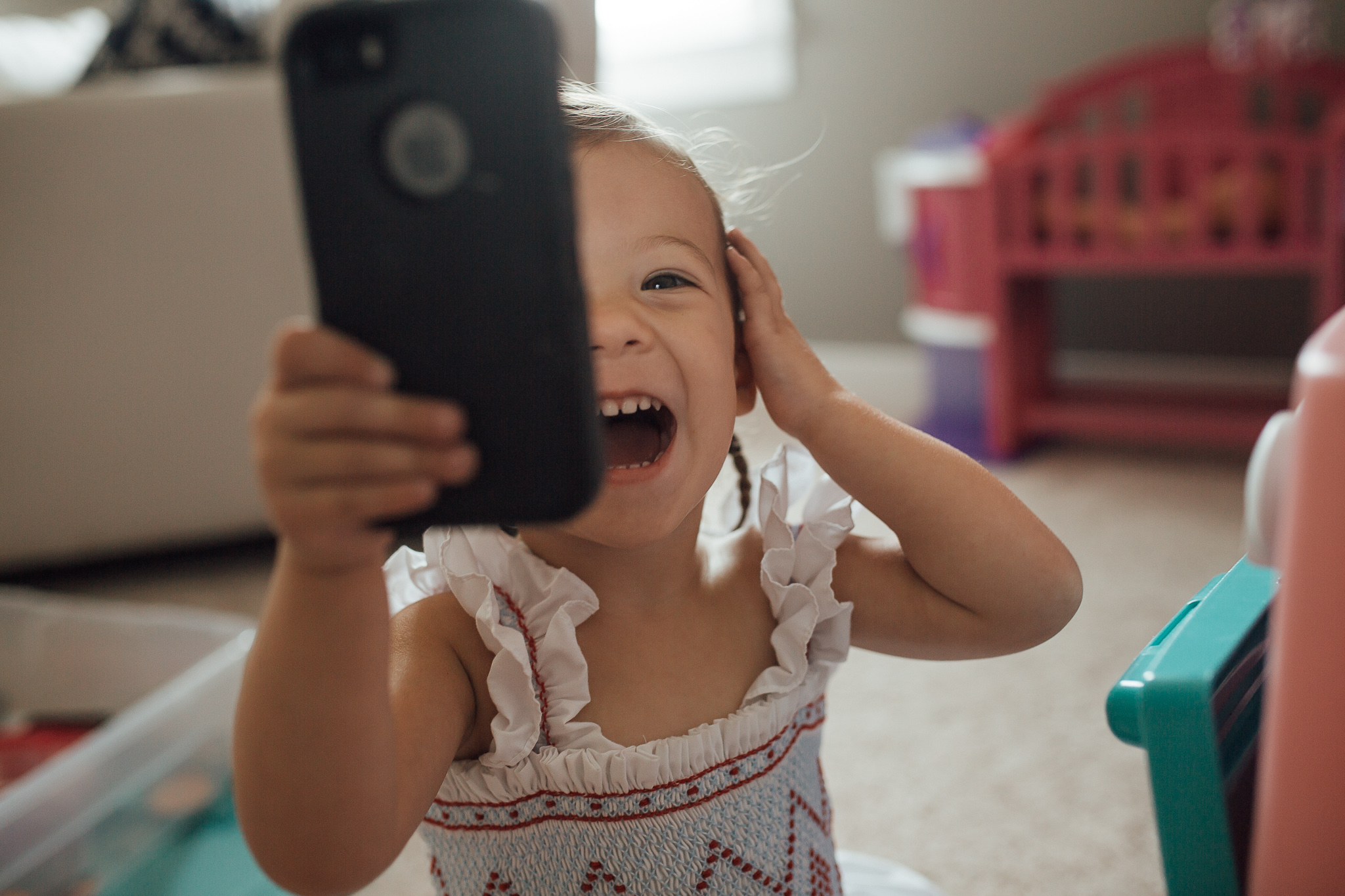 """Okay, so this is probably my favorite picture from my in-home session with Logan. It may not be """"perfect"""" and she may have my big ugly iphone smack dab in the middle of the photo, but look how happy she is! This little snapchat queen knows how unbelievably cute she is."""