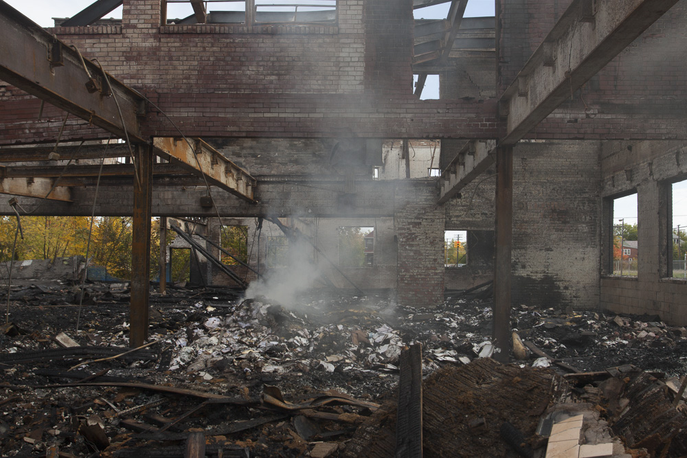 A fire in a warehouse continues to smolder several days after the fire was put out.