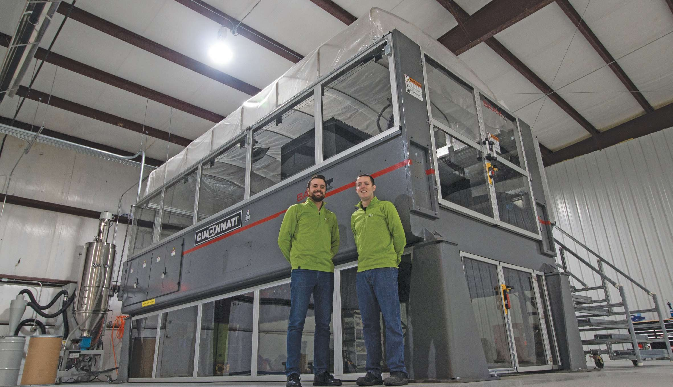 Andrew Bader and Austin Schmidt stand in front of the Big Area Additive Manufacturing machine that is the basis for their business.