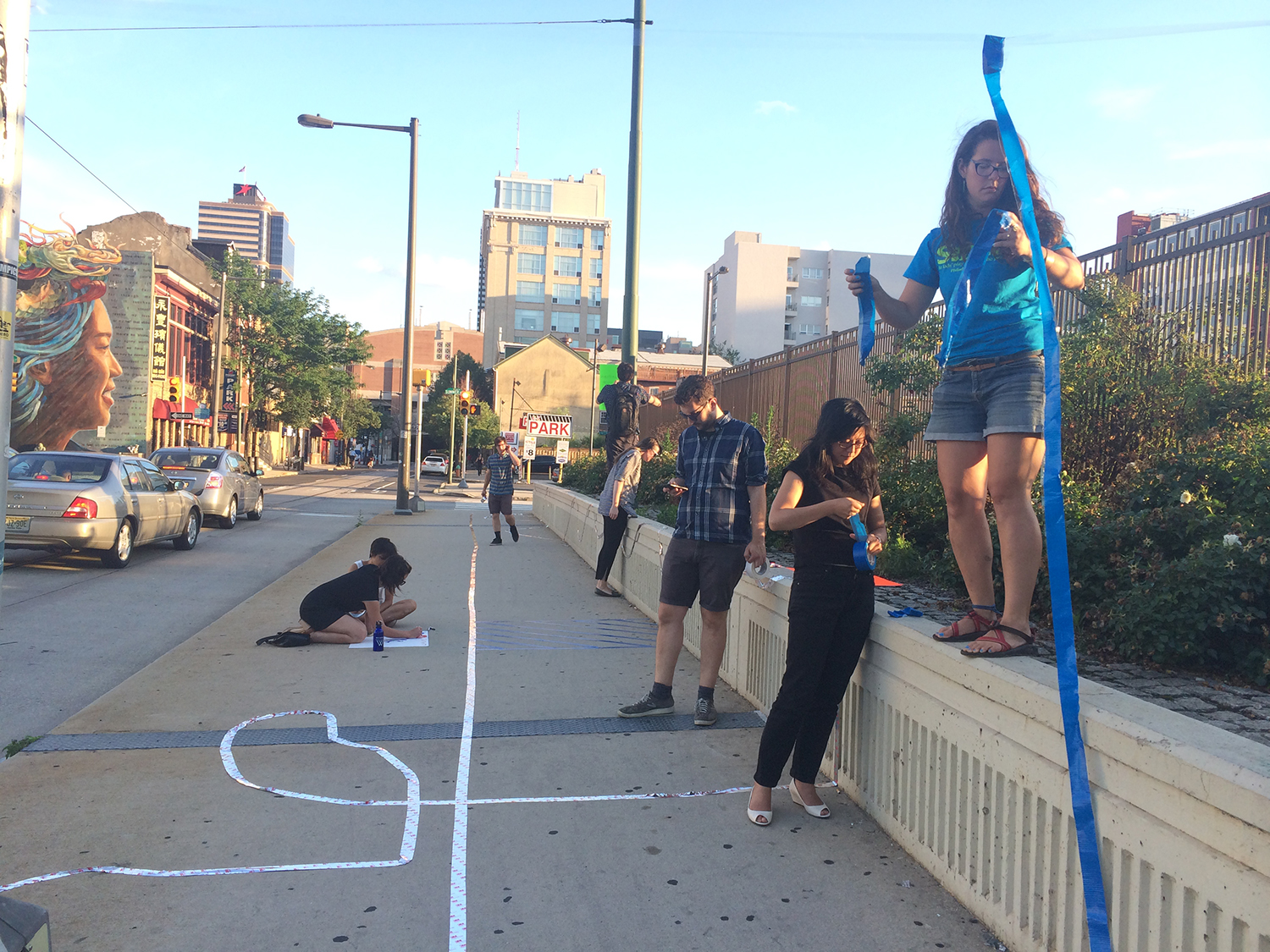 Slow Lane - | A STRETCH OF SIDEWALK COMPLETE WITH HOPSCOTCH, A DANCE STATION, STREAMERS, AND SIGNS ENCOURAGING PEOPLE TO SLOW DOWN. |