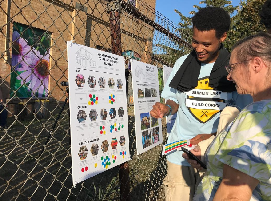 Build Corps member walks a resident through the voting process asking what residents want to see in the Pump House