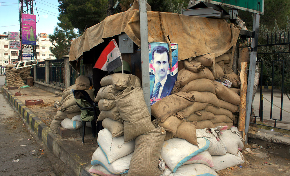 A poster of Syria's president Bashar al-Assad at a checkpoint on the outskirts of Damascus, Jan. 14 2012. Photo by Voice of America Middle East correspondent Elizabeth Arrot.
