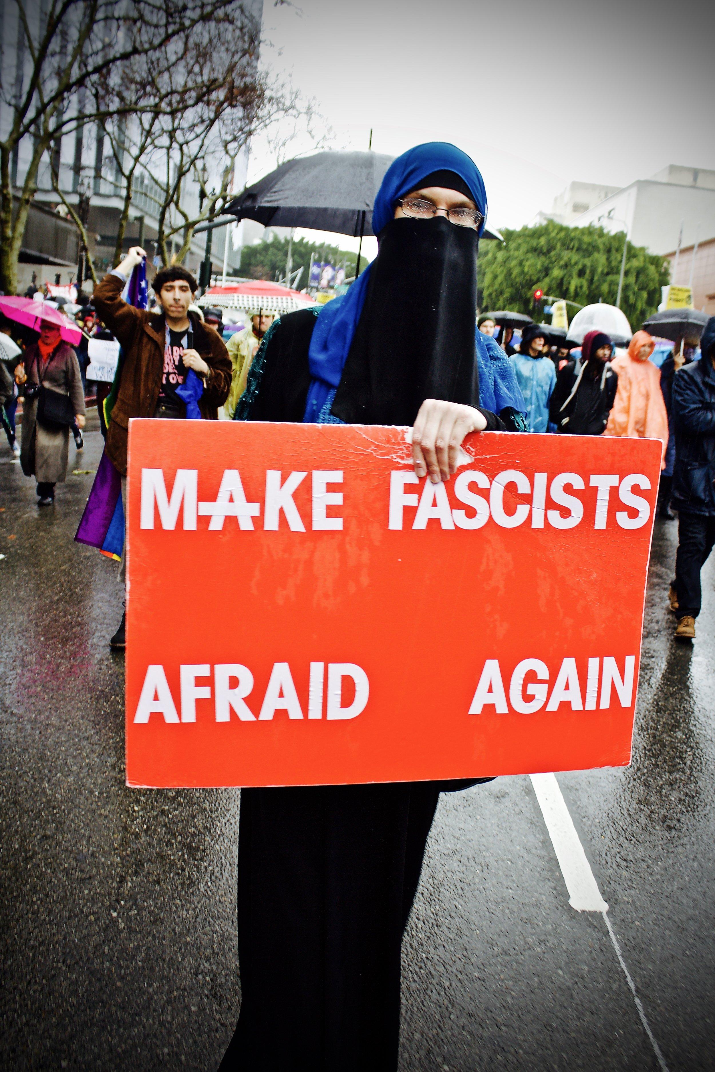 Sumayyah Dawud, 32, marches down a rain-soaked street on Muslim garb.