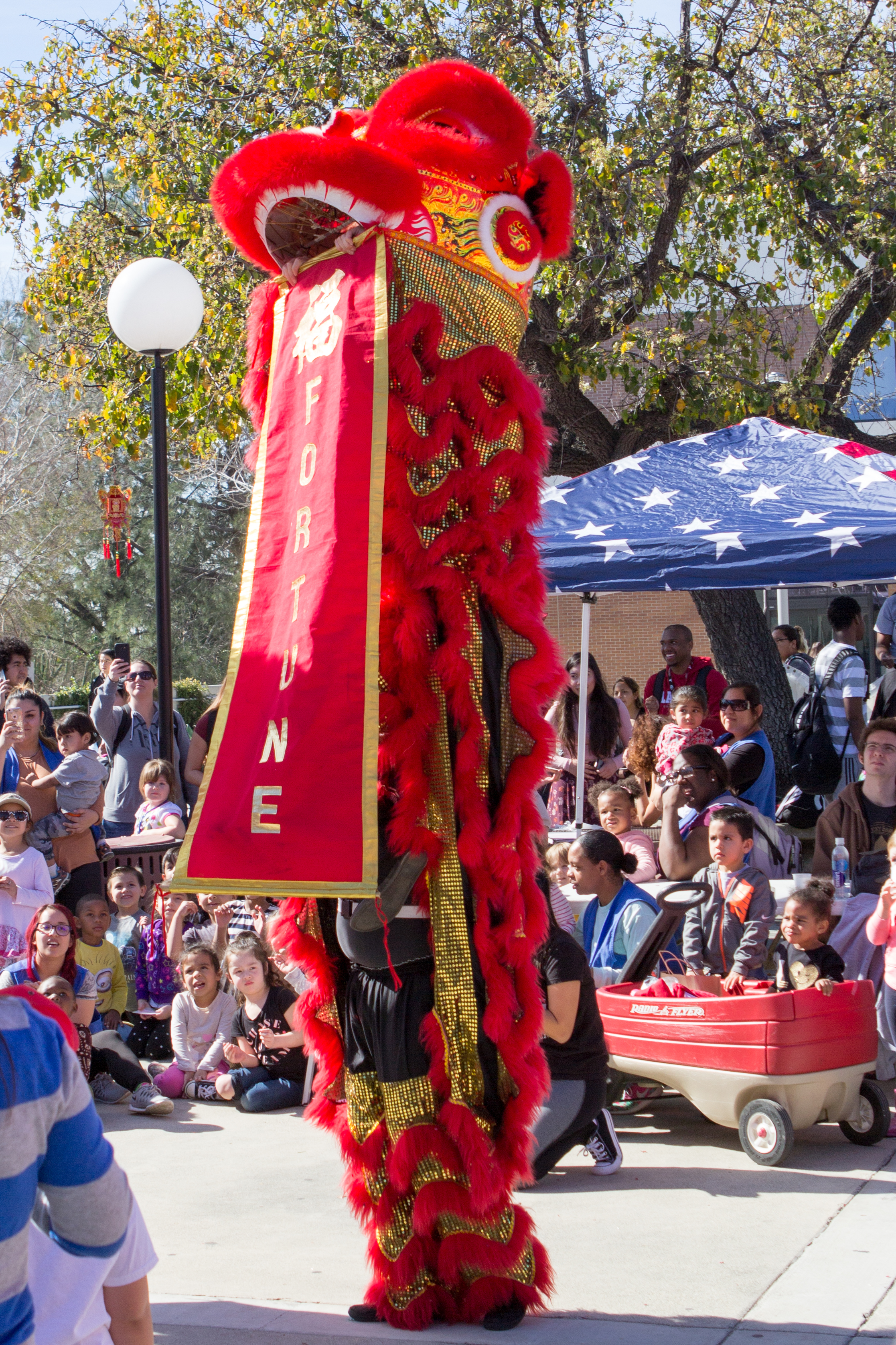 """Red lion performers unfurl a banner with the word """"Fortune"""" written upon it as part of the finale of the Lion Dance on   Wednesday, Feb. 1, 2017. Photo by Christopher Santee."""