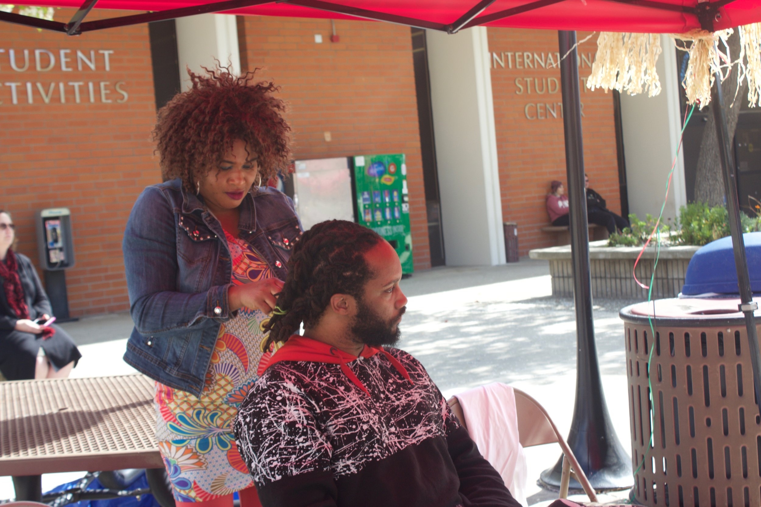 Hair braiding was one of many more activities at the African Village Event on Feb. 22. Photo by Esmerelda De Santiago